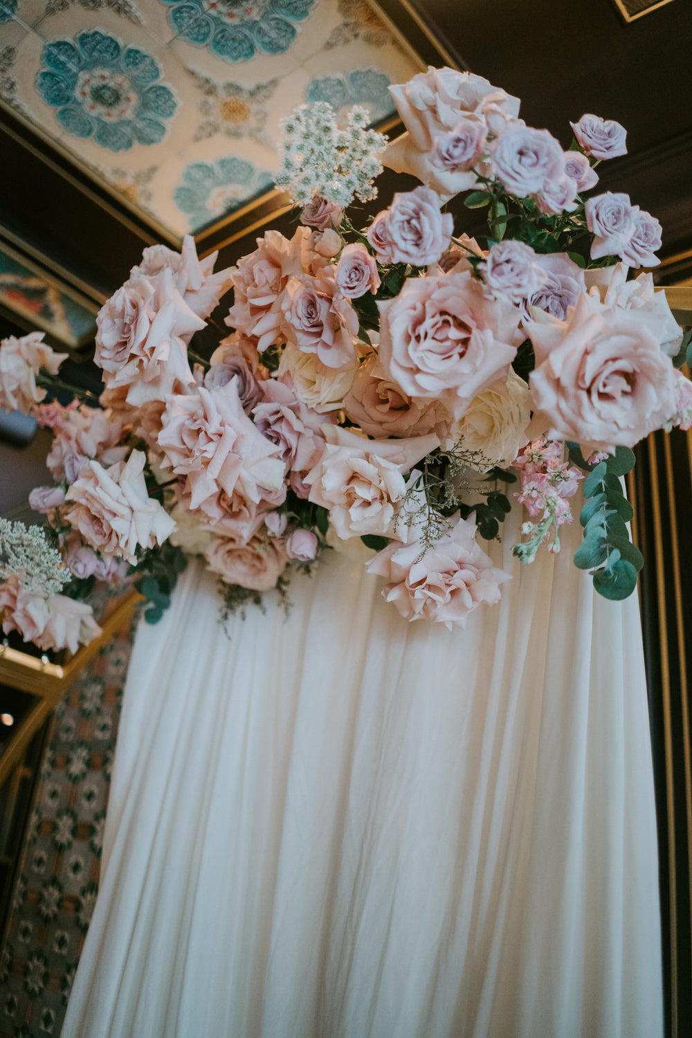 Floral arrangement for circle arch at surprise fiance wedding proposal with dusty pink floral palette and eucalyptus in front of white drape cloth
