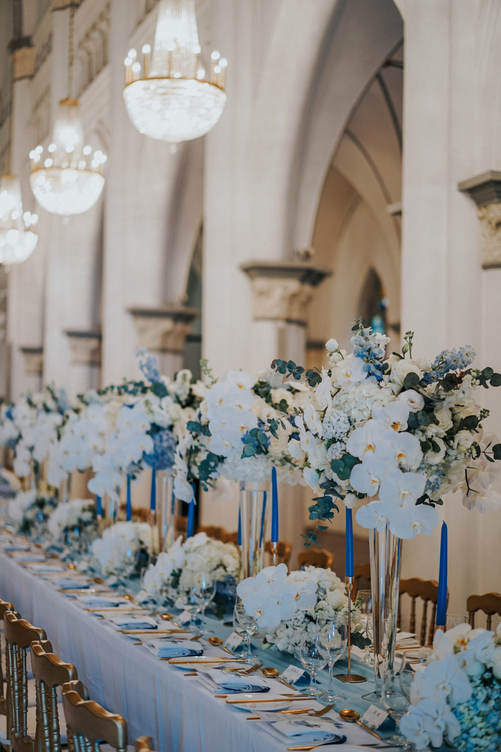 Long dinner table styled with blue candles in gold candlesticks and white and blue floral arrangements at a solemnization