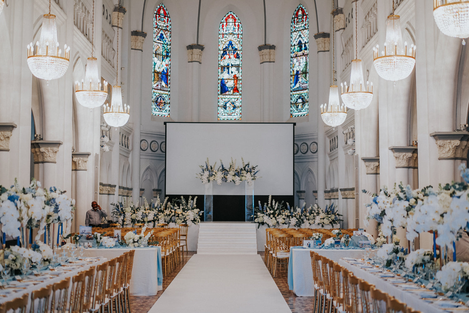 CHIJMES chapel hall with stained glass. White orchids arrangement on the main stage atop some stairs at City Hall