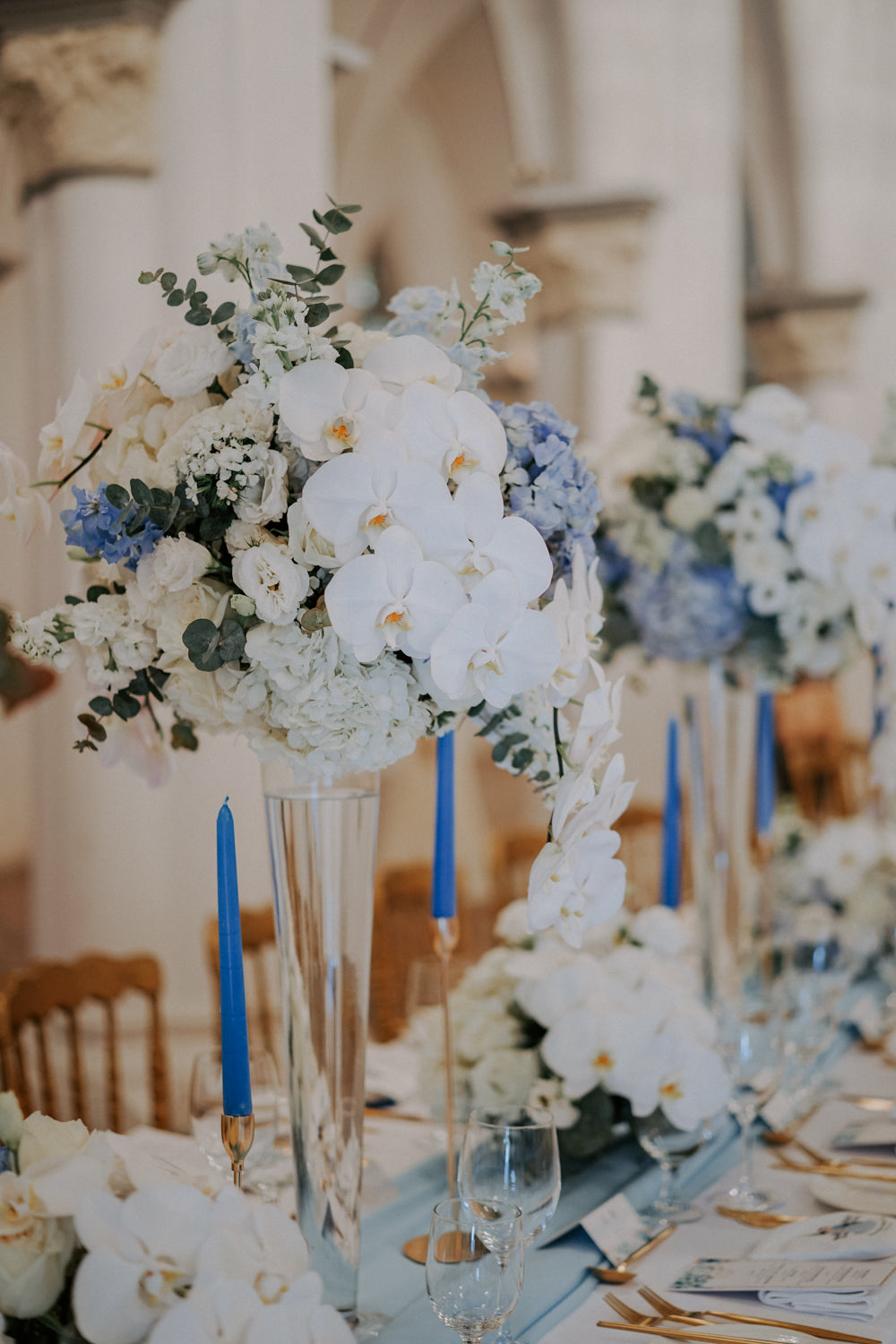 Close-up of white orchids in a floral arrangement styled in a tall, crystal vase on dining table at a CHIJMES wedding