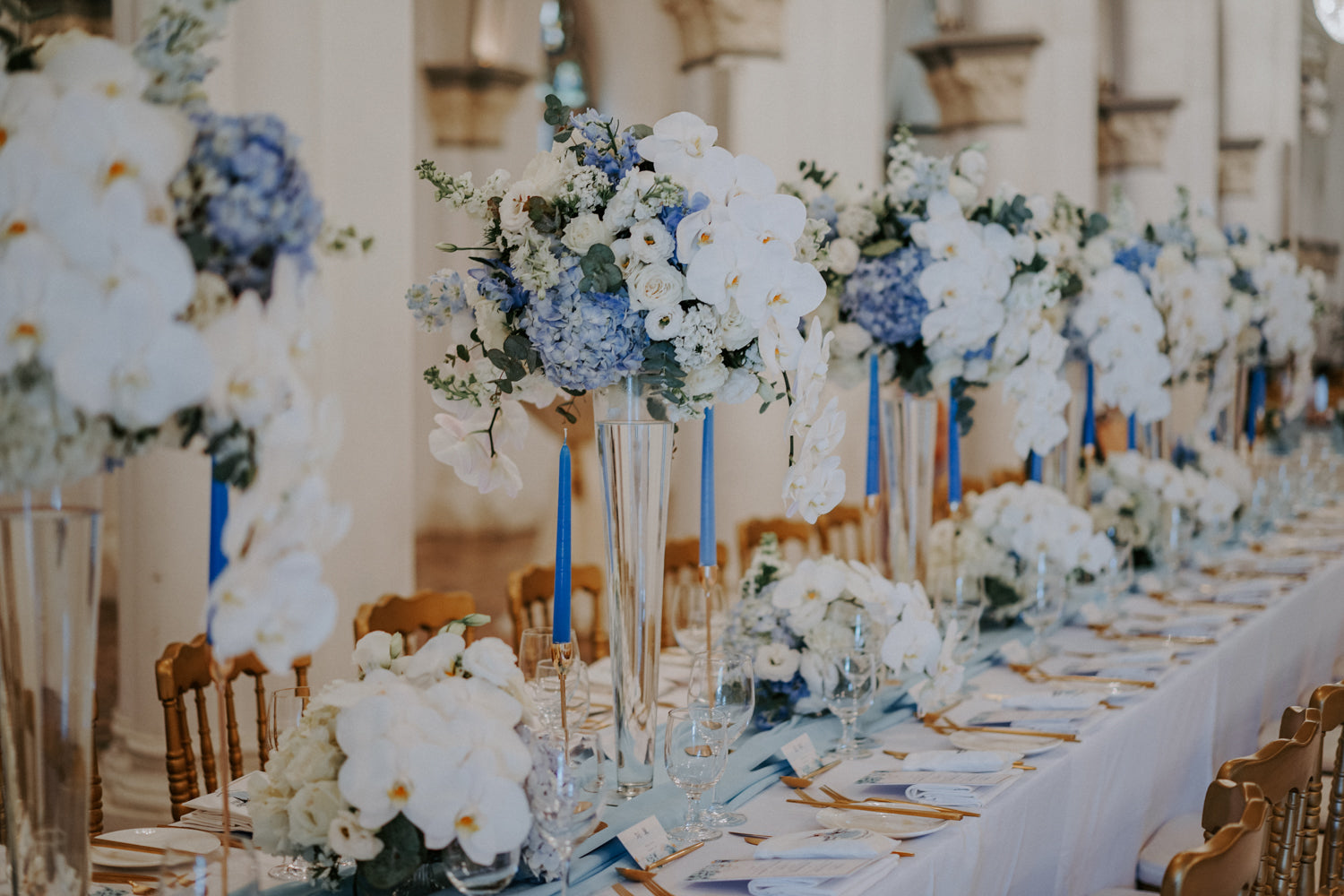 Tall and short floral arrangements in white and blue on a long, white wedding dining table in CHIJMES hall