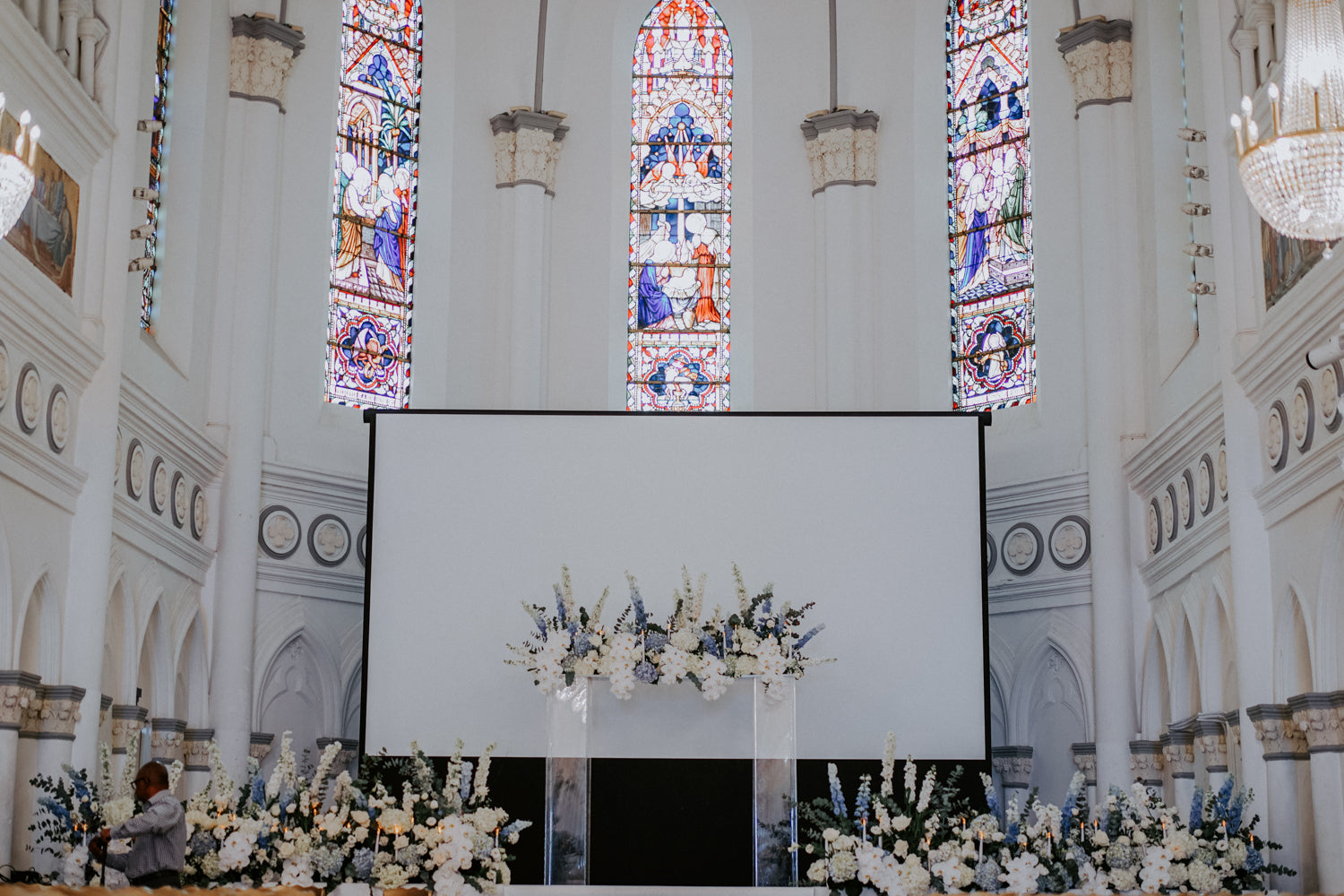 White screen in a CHIJMES chapel hall with stained glass and white, blue flower arrangements