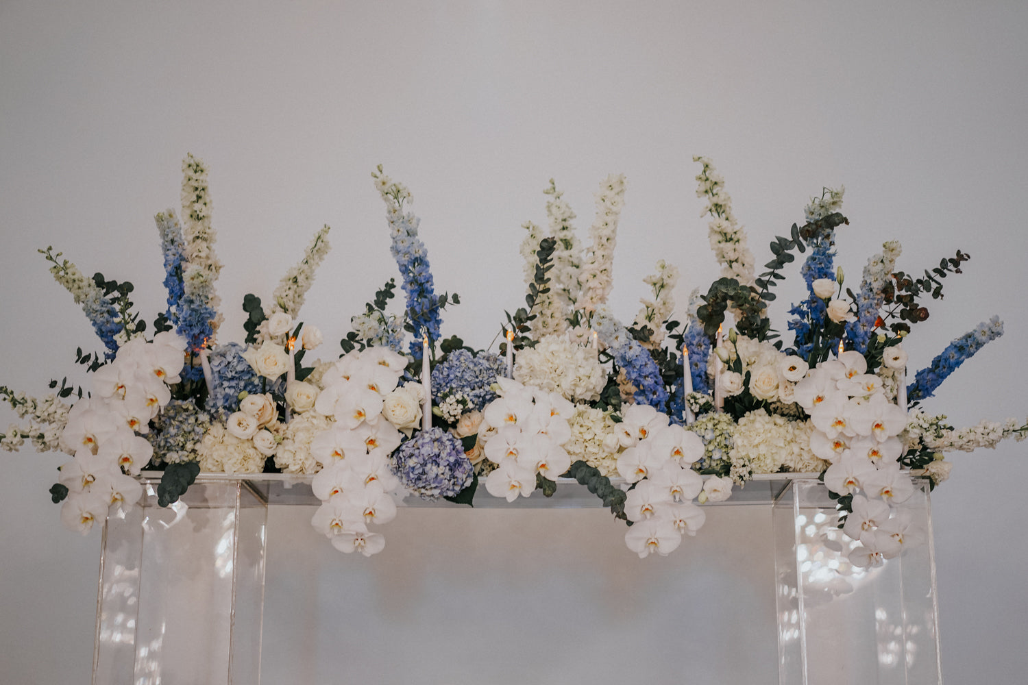 Styled orchids, hydrangeas, delphiniums, and buttercups in white and shades of blue atop acrylic stands for CHIJMES weddings