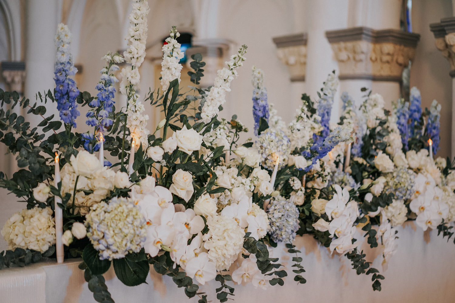 Close-up of styled white and blue flowers atop acrylic stands with candles at a romantic wedding at CHIJMES