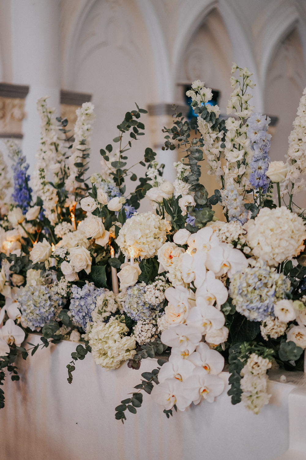 Close-up of styled white orchids with white and blue delphiniums and hydrangeas at dreamy CHIJMES solemnization