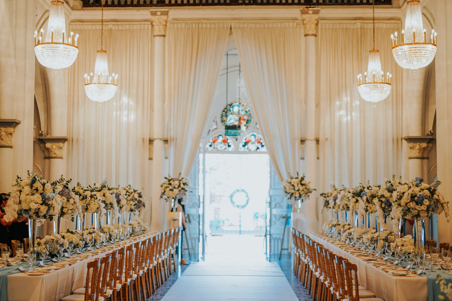 Doorway of CHIJMES hall with light streaming in on long, white tables of floral arrangements. Chandeliers hang next to ivory curtains