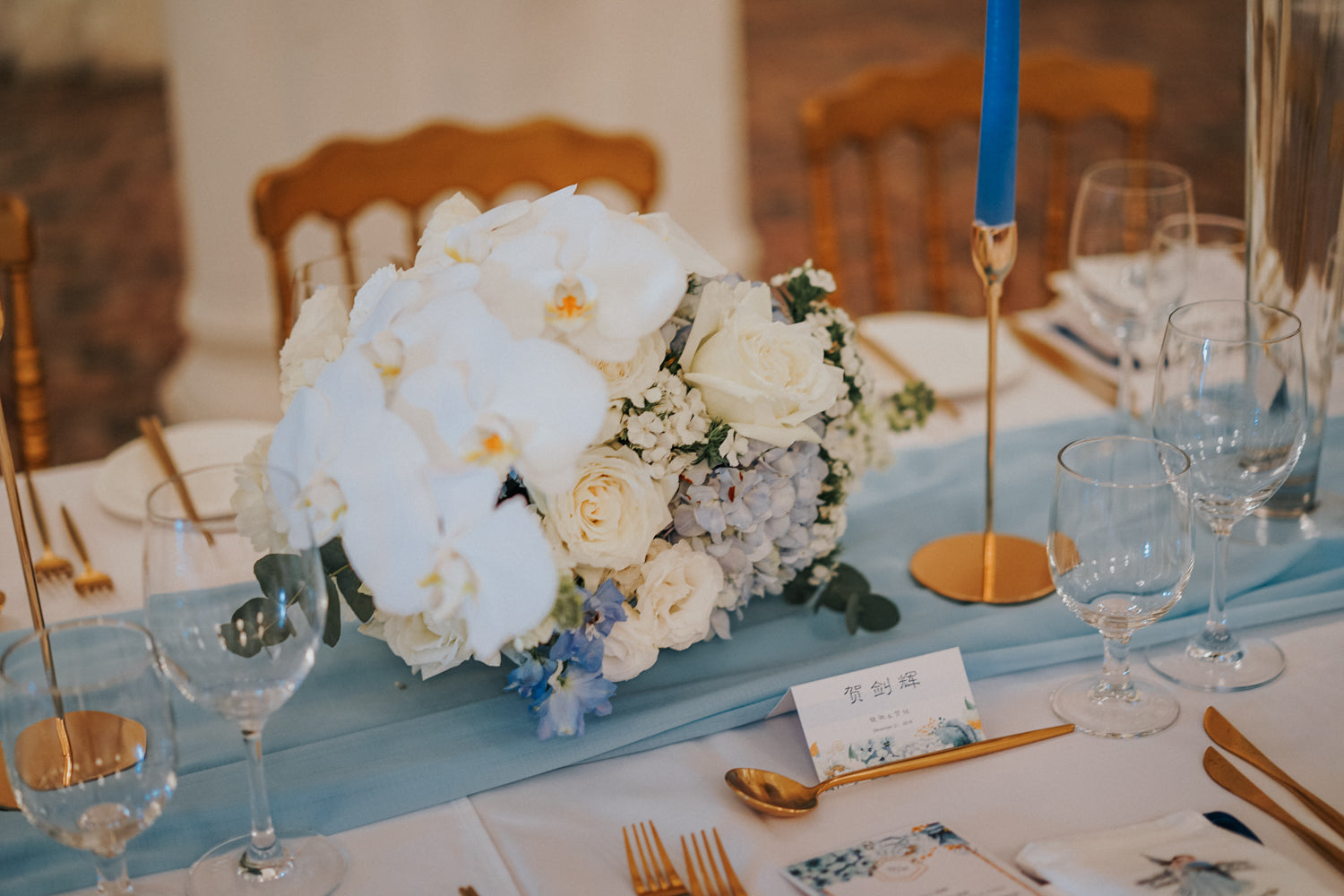 Floral arrangement of white orchids and roses with blue hydrangea on a white table with baby blue table runner at a solemnisation