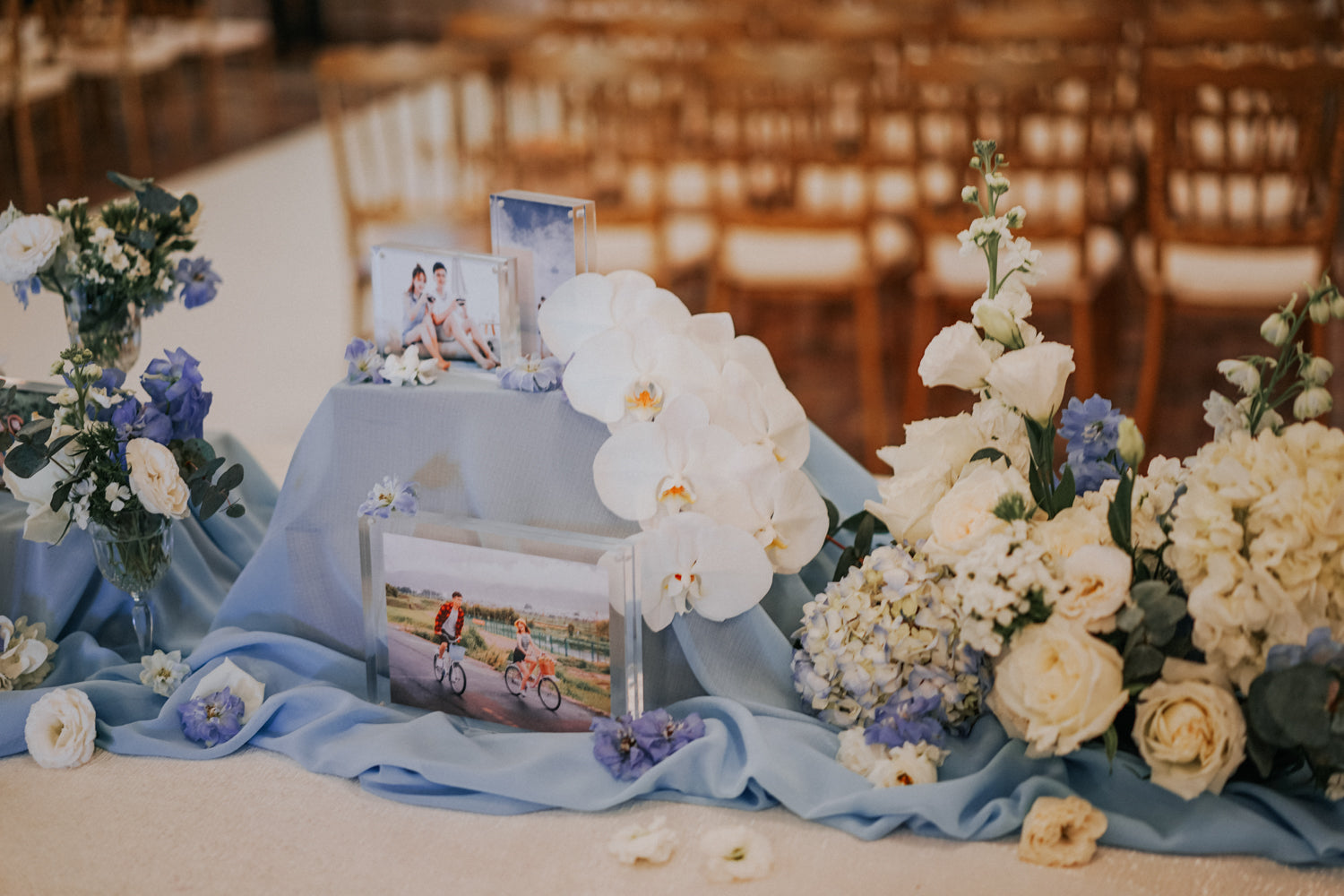 Couple photos in acrylic frames, positioned on baby blue table runner, decorated by white orchids and other flowers in blue and purple for weddings at CHIJMES