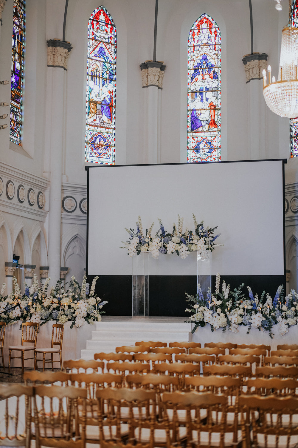 Gold chairs arranged in CHIJMES chapel hall facing a screen and a seasonal flower styling for a solemnization