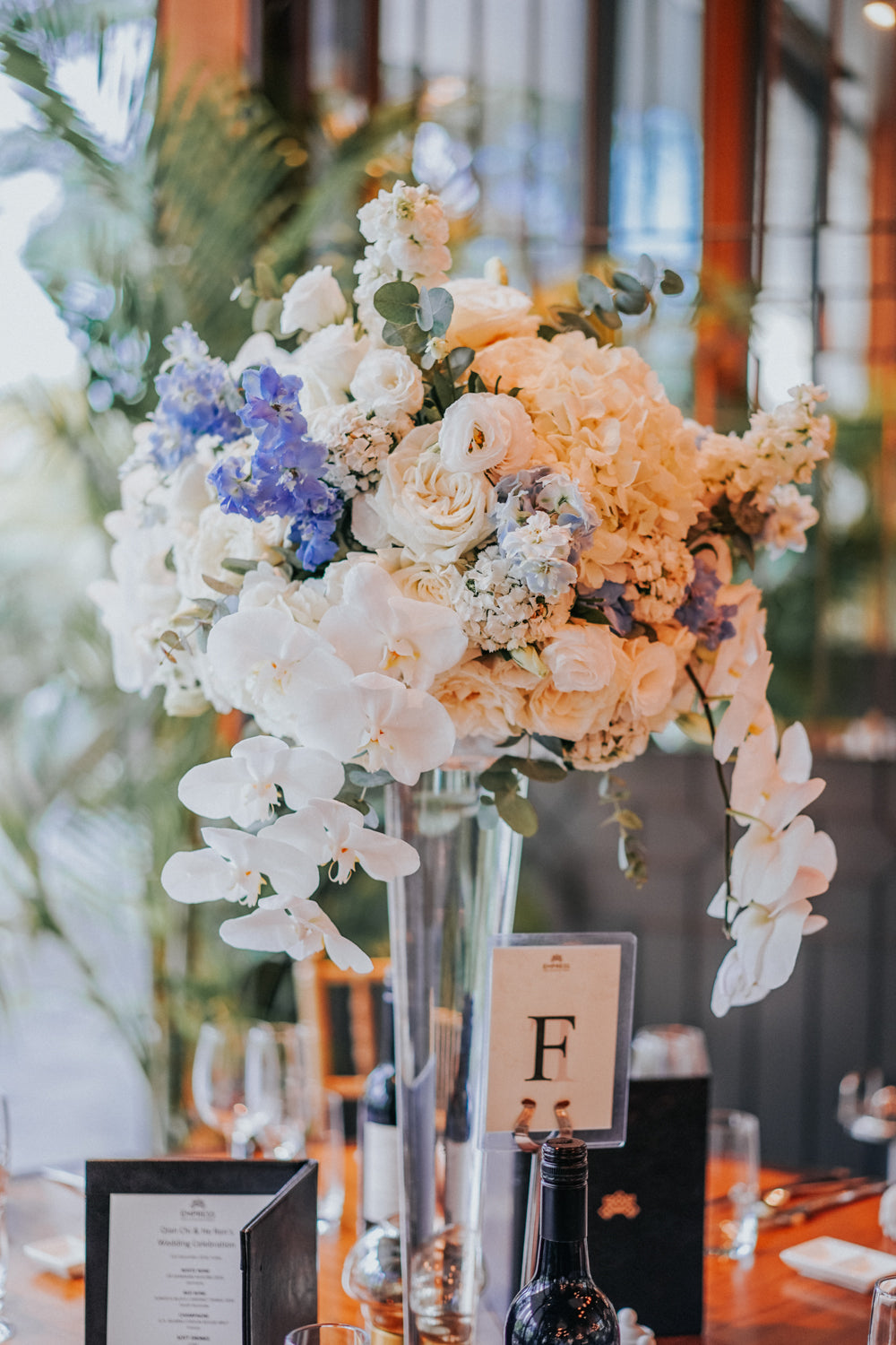 """Close-up of white orchids and buttercup anemones on a dining table marked """"F"""" in CHIJMES hall for a wedding"""