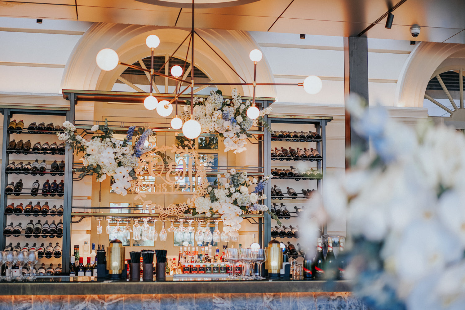 ACM's Empress bar counter decorated with white florals next to wine bottles