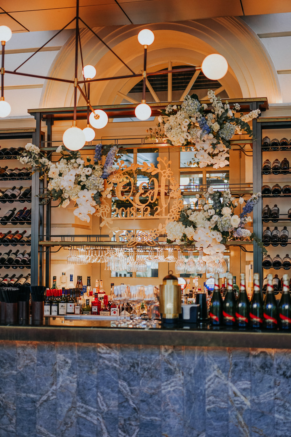 Warmly lit marble bar counter decorated with white orchids, blue hydrangeas, eucalyptus next to wine bottles and glasses at ACM Empress restaurant