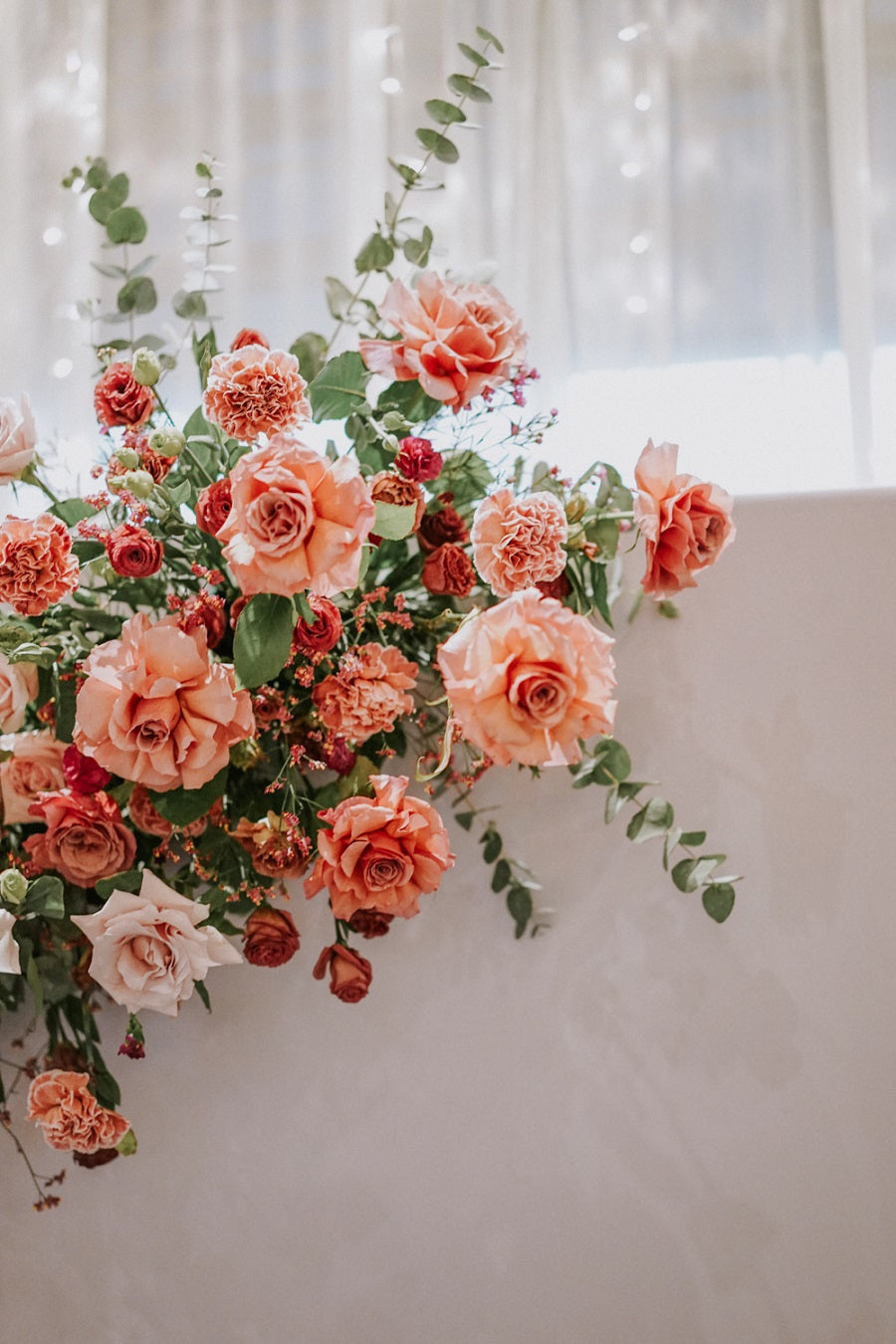 Close up of blush pink and red fall wedding decor of flowers at Singapore PARKROYAL COLLECTION Pickering Hotel