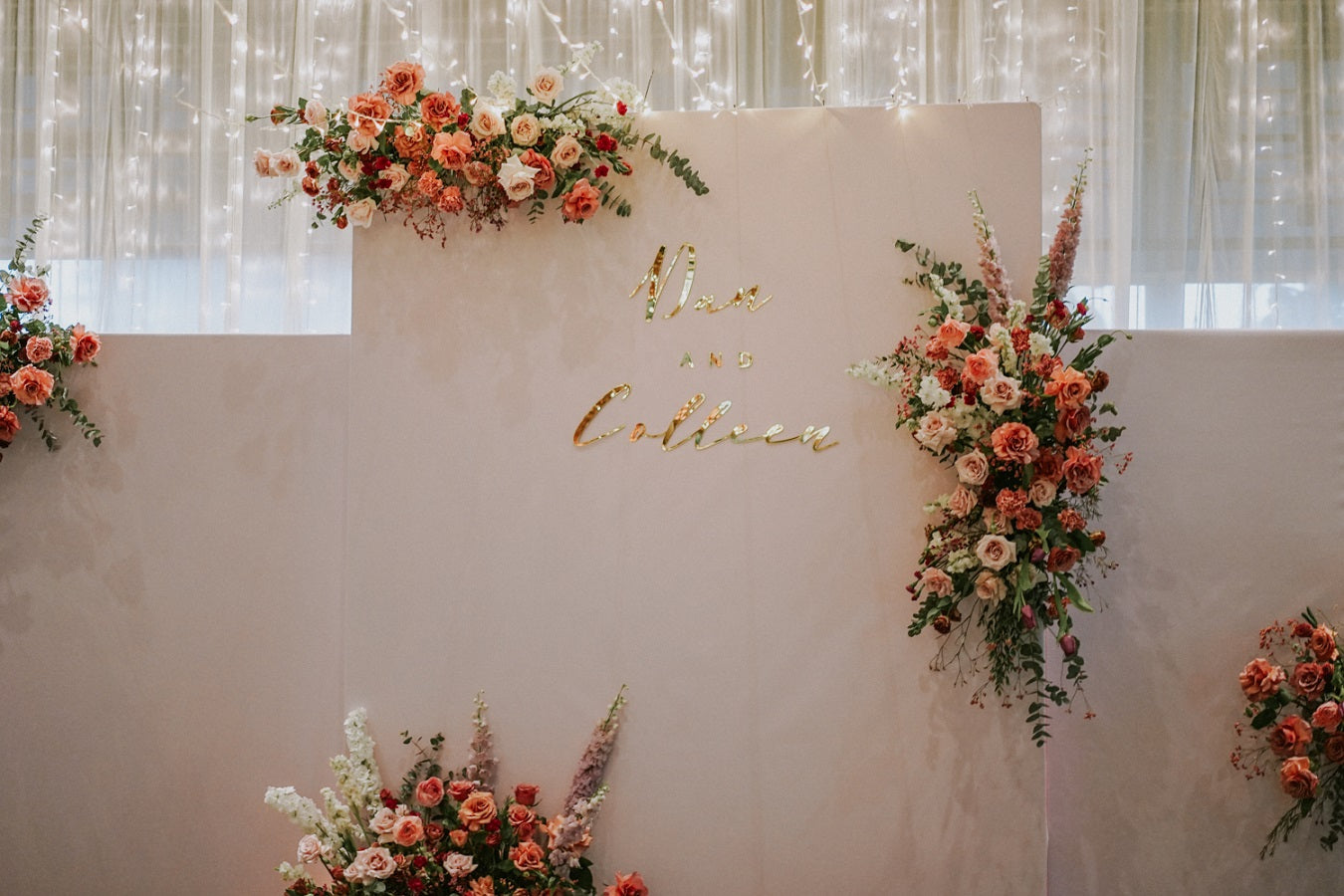 Freestanding hanging floral installation on white backdrop with fairy lights for wedding stage at Park Royal Hotel Singapore