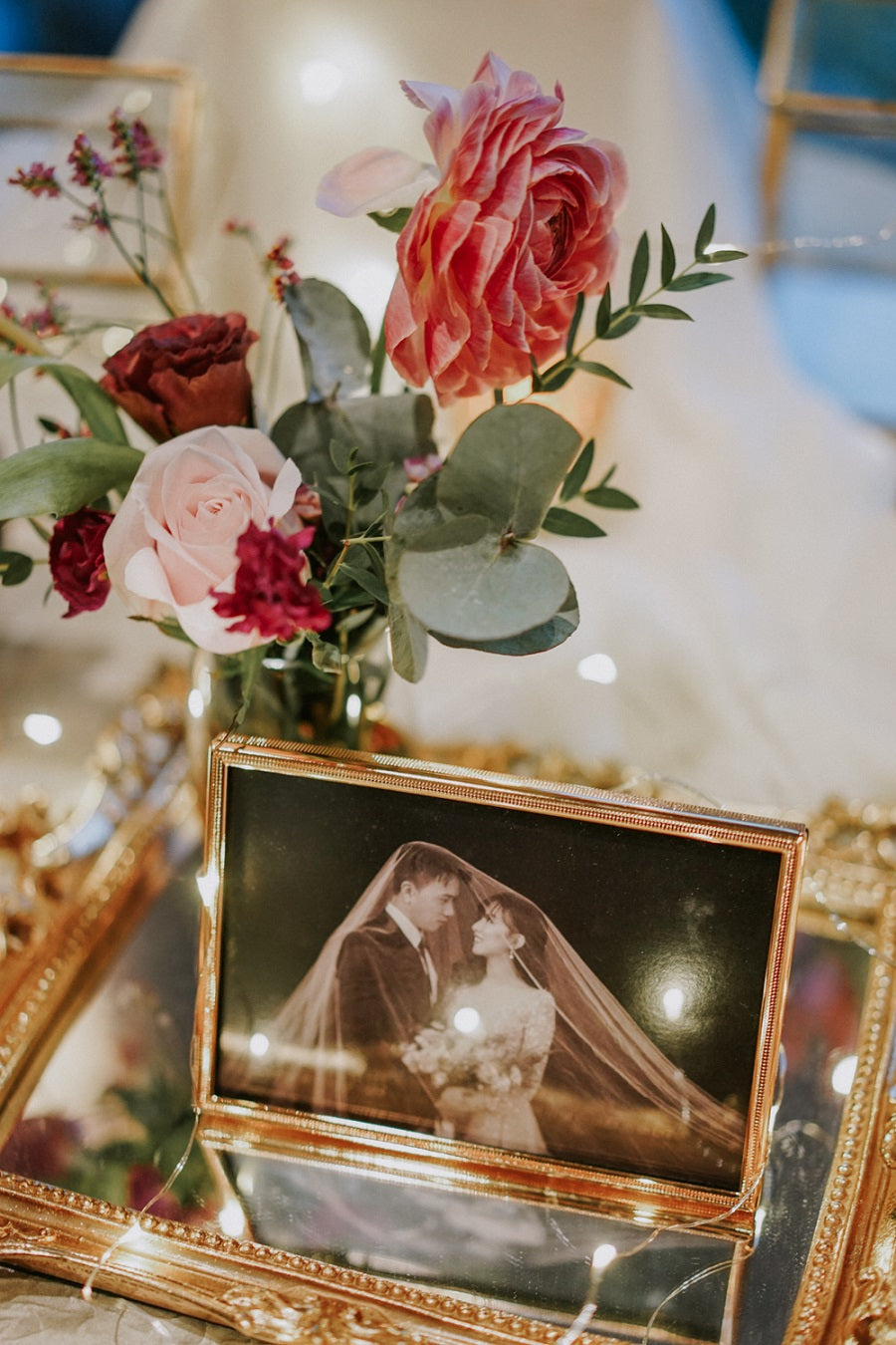 Eucalyptus with blush rose arranged on mirror prop for bespoke wedding photo table styling