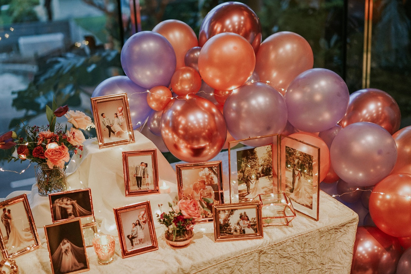 Wedding photo table props for table styling decor at wedding reception with balloons of metallic shades and premium photo gallery setup