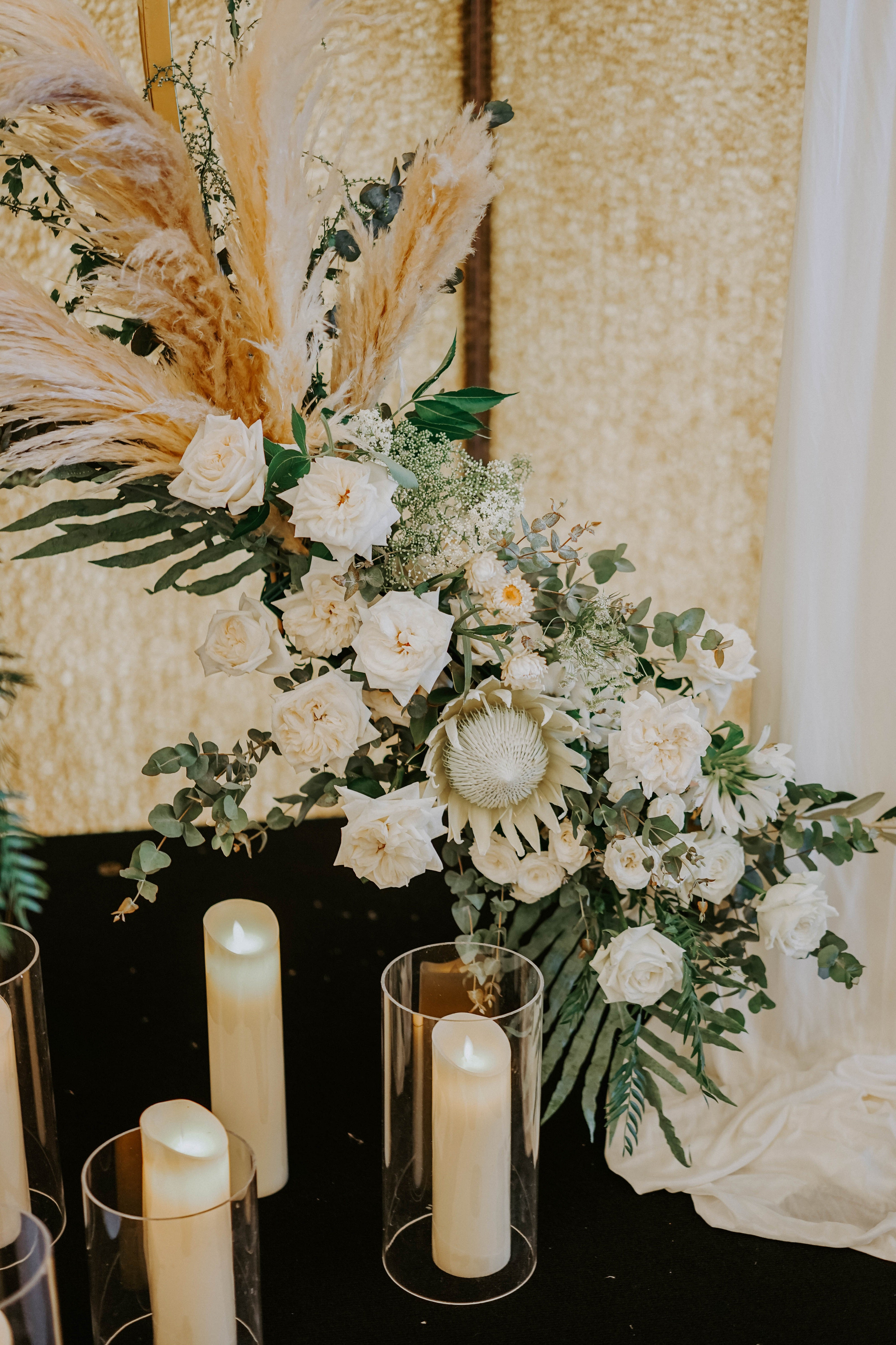Unique white wedding flowers decoration at SICC Country Club with customised colour palette for blooms with matching candles set