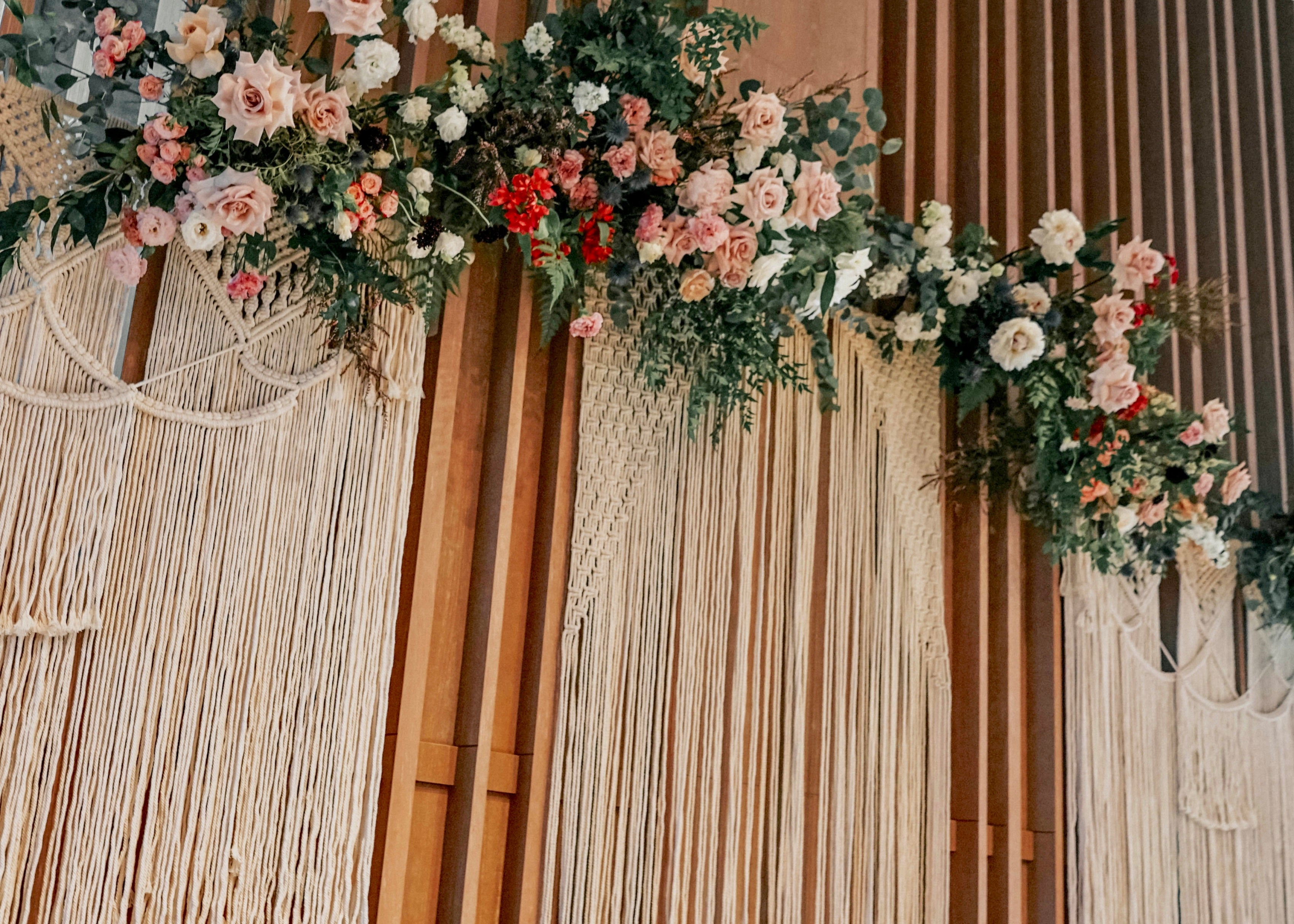 Close up of yarn boho macramé backdrop accentuated with eucalyptus, peonies, roses, Scabiosa, Alstromeria, Eustoma, Didiscus, Ranunculus, Queen Anne Lace and Astibile