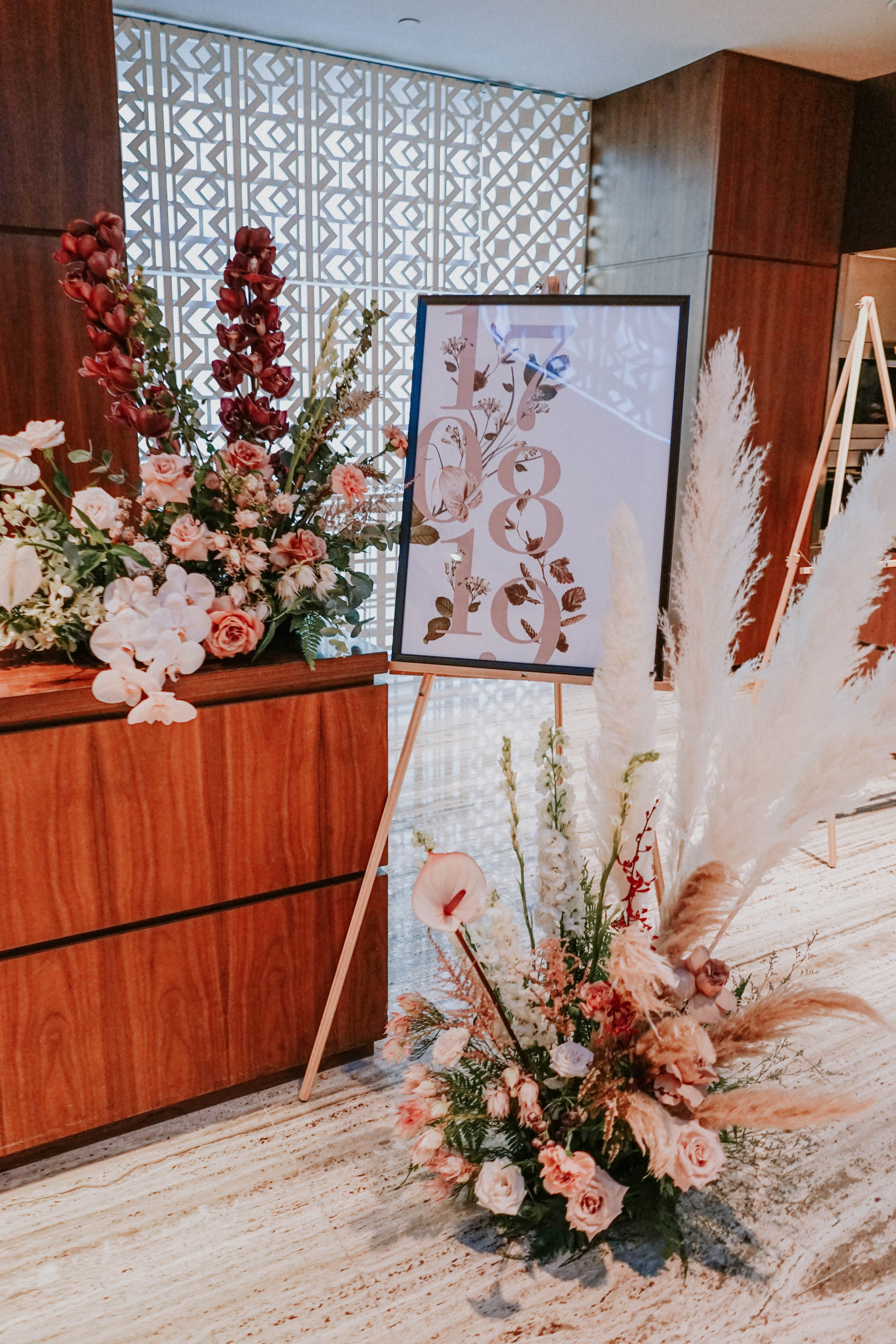 Romantic minimalistic welcome signage for wedding ceremony decorated with orchids and pampas floral installations at Grand Hyatt Singapore