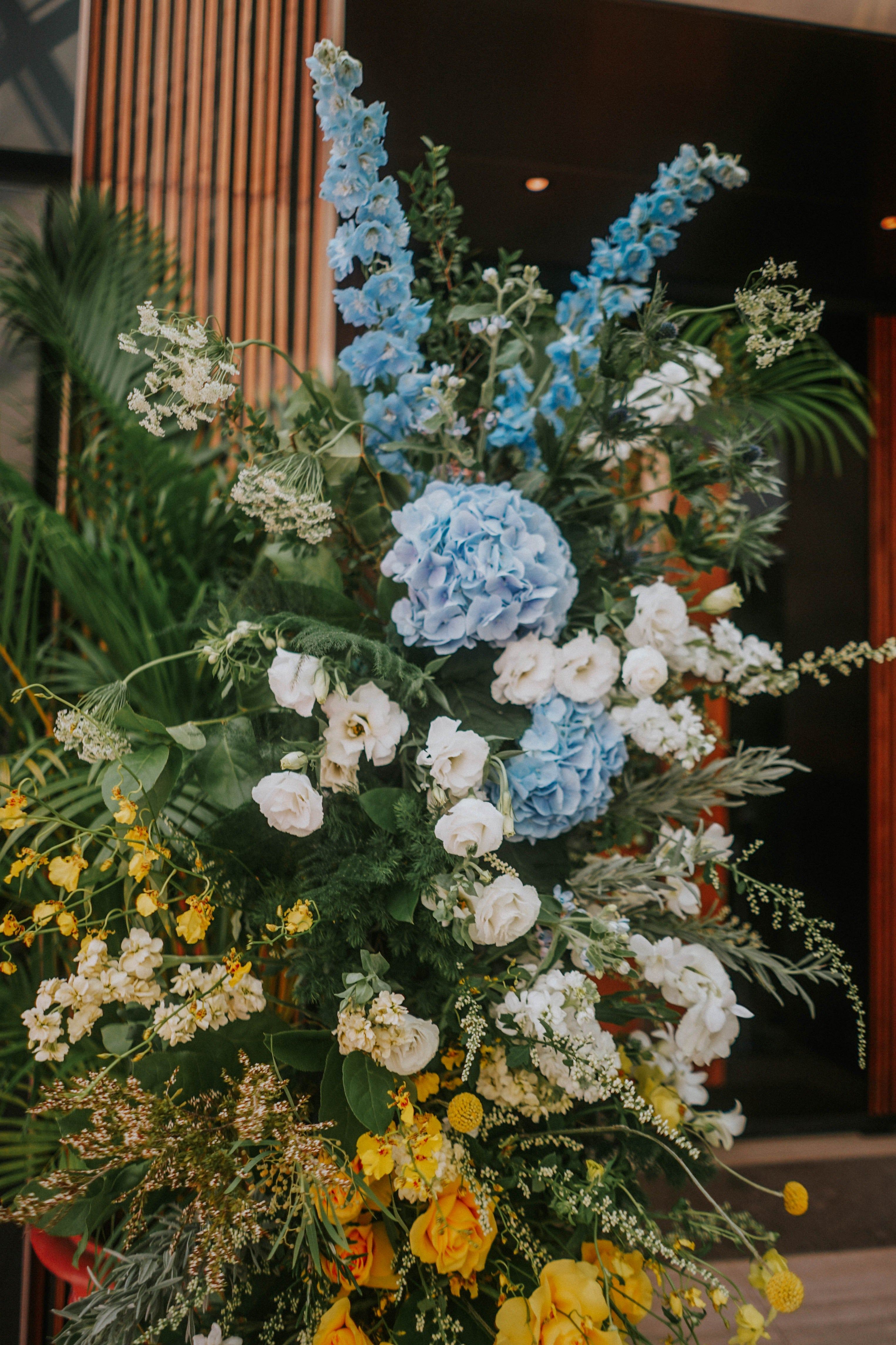 Tall mobile floral display at Wesley Methodist Church Singapore with blue and yellow colours and tropic ferns