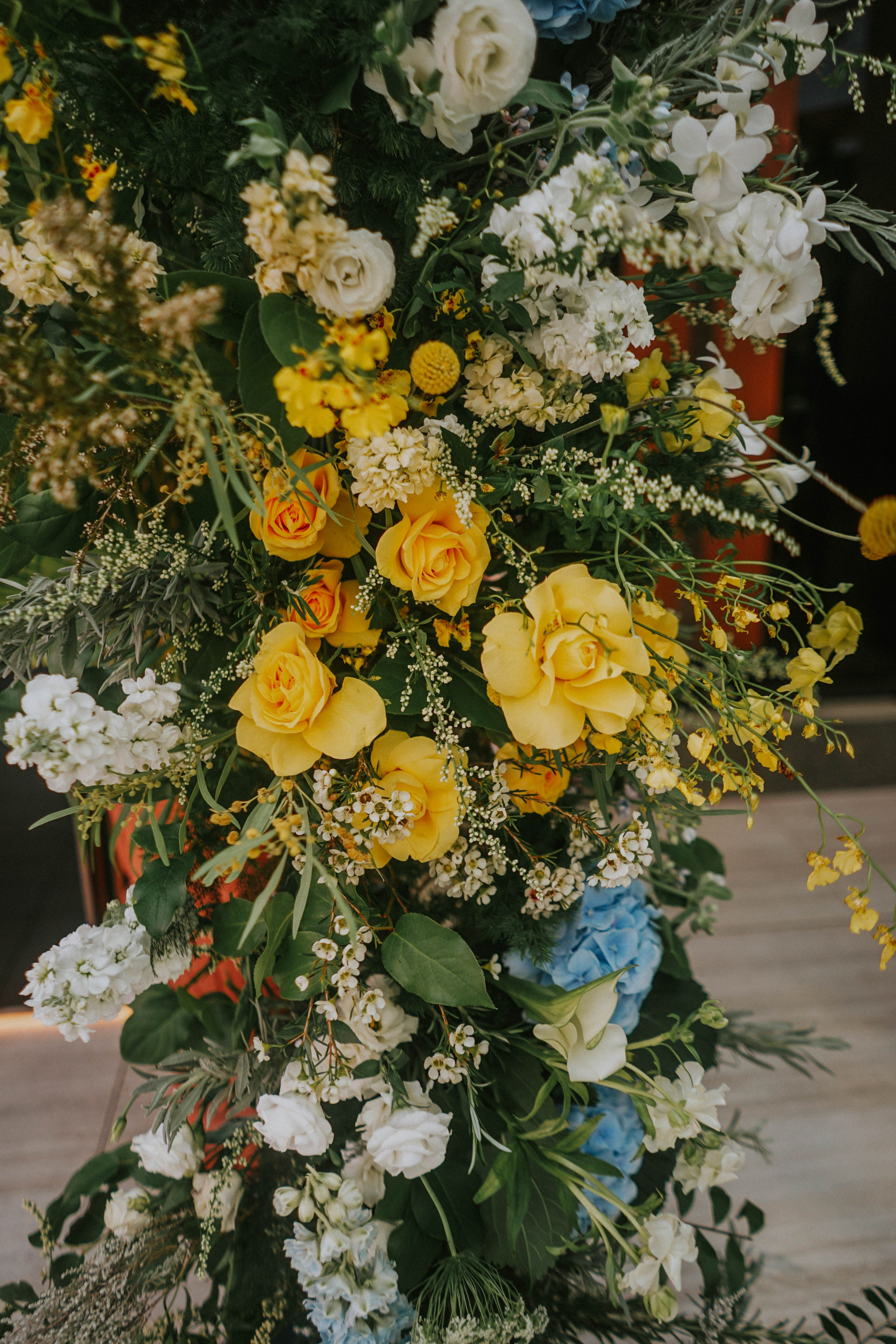 Close up shot of yellow roses, delphiniums, white queen anne's lace, and tropical ferns for a wedding ceremony at Wesley Methodist Church chapel