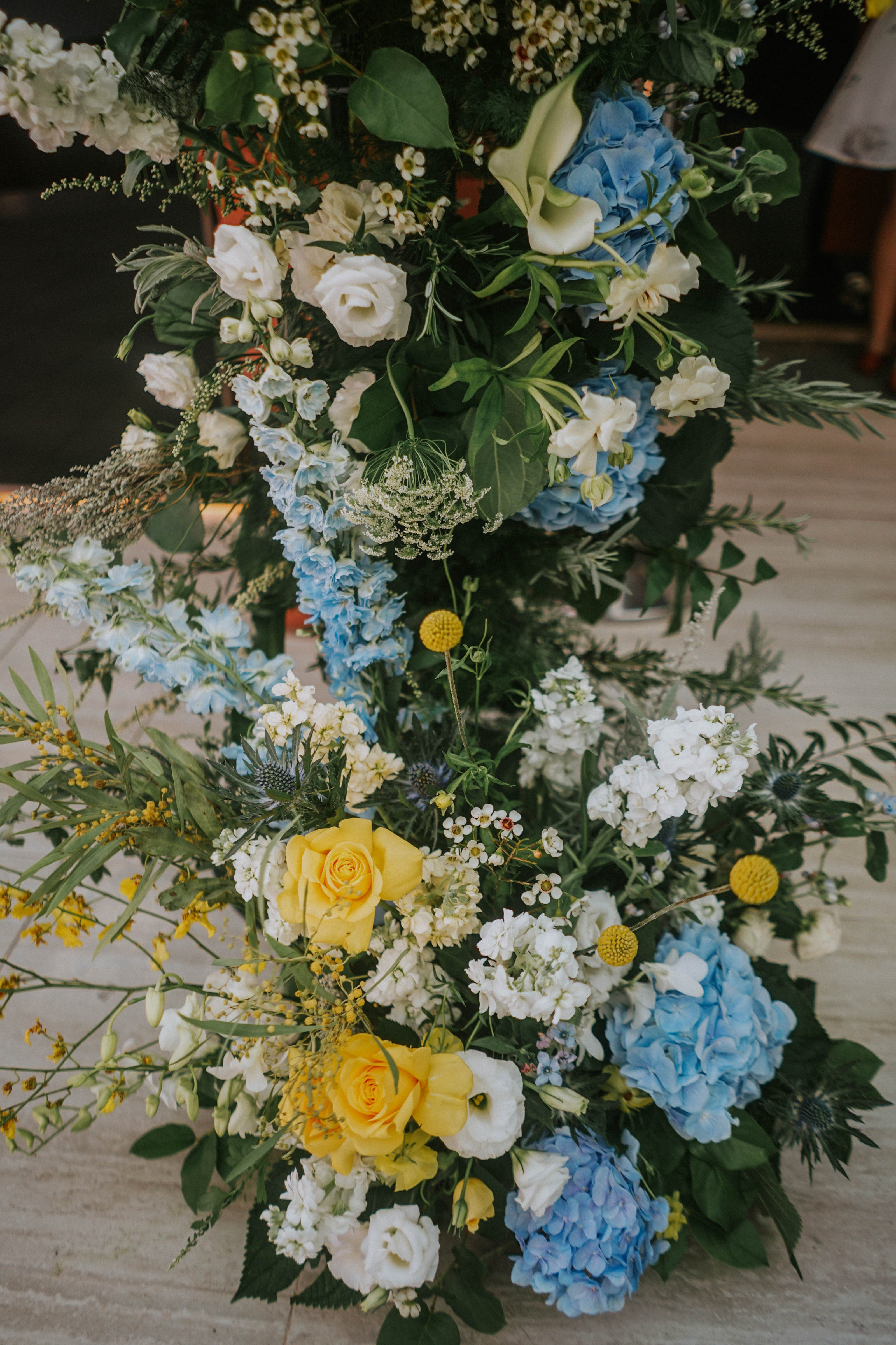 Blue hydrangeas nestled among white queen anne's lace and eustomas, put together with yellow roses and queen anne's lace near Fort Canning Park at Wesley Methodist Church for solemnisation ceremony