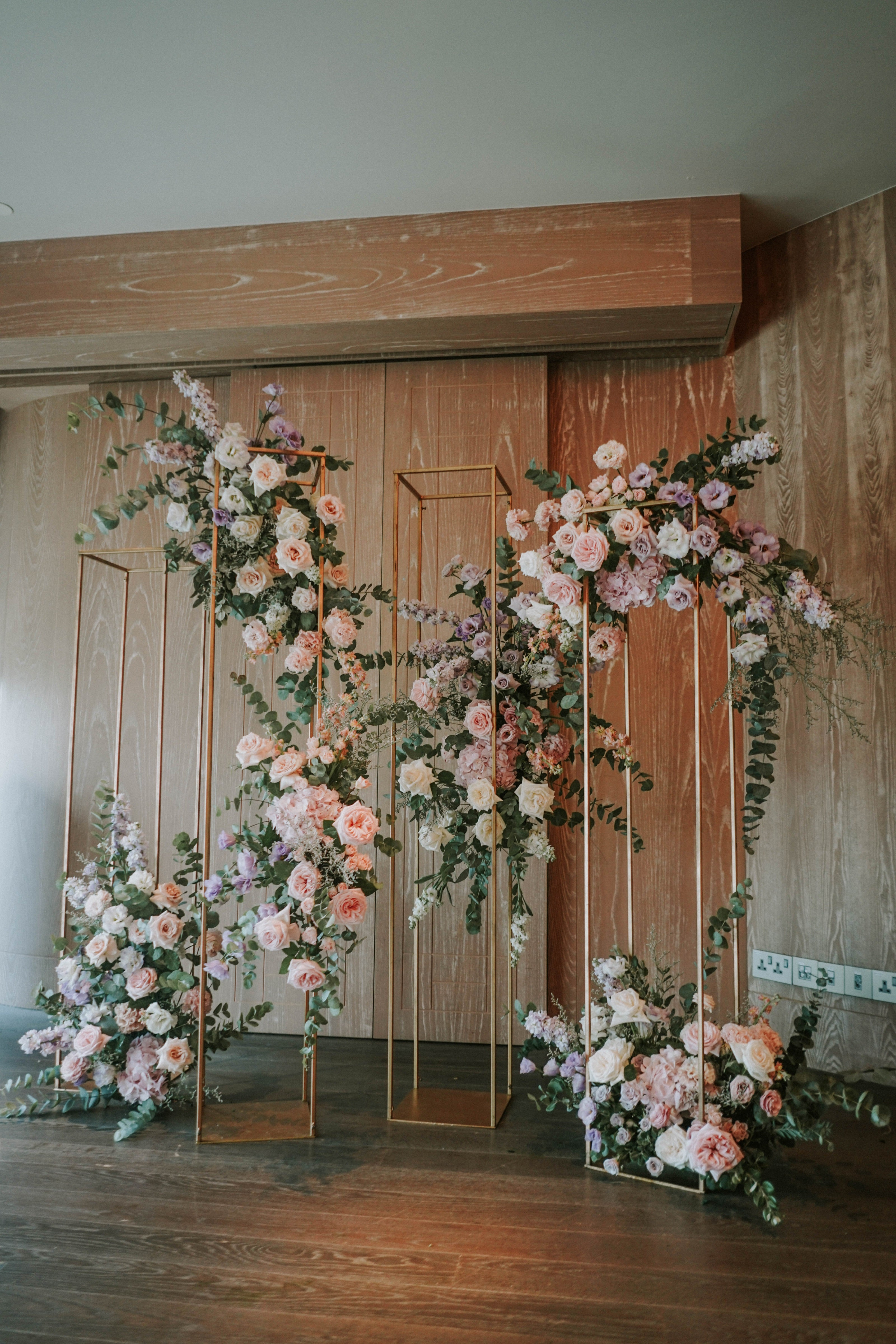 Free standing floral structures for backdrop and versatility with trailing eucalyptus leaves and roses, mattiolas, hydrangeas in shades of pink and purple