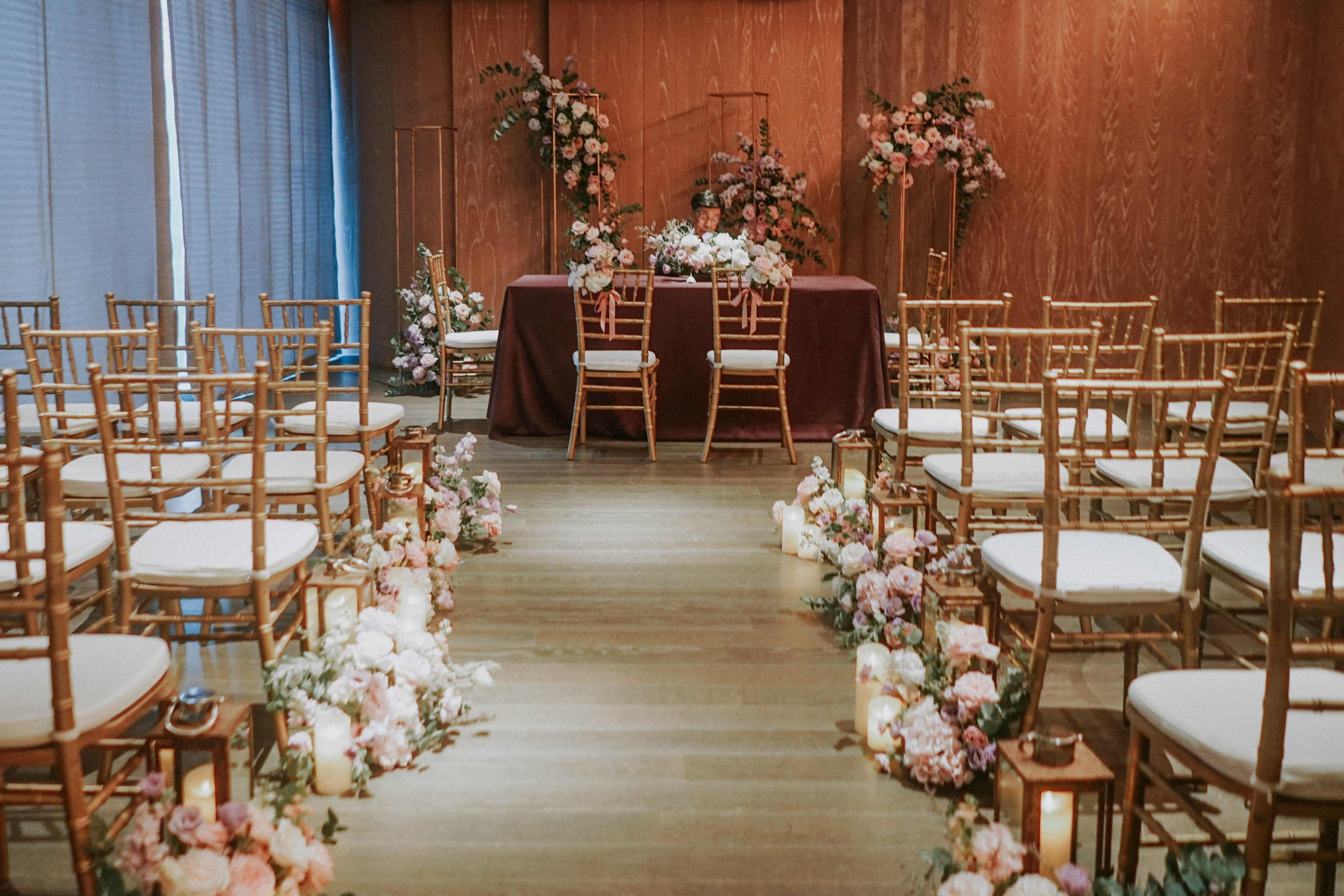 Gold Tiffany chairs with white cushions in intimate solemnisation ceremony hall lined with romantic floral hedges at Hyatt Andaz Singapore
