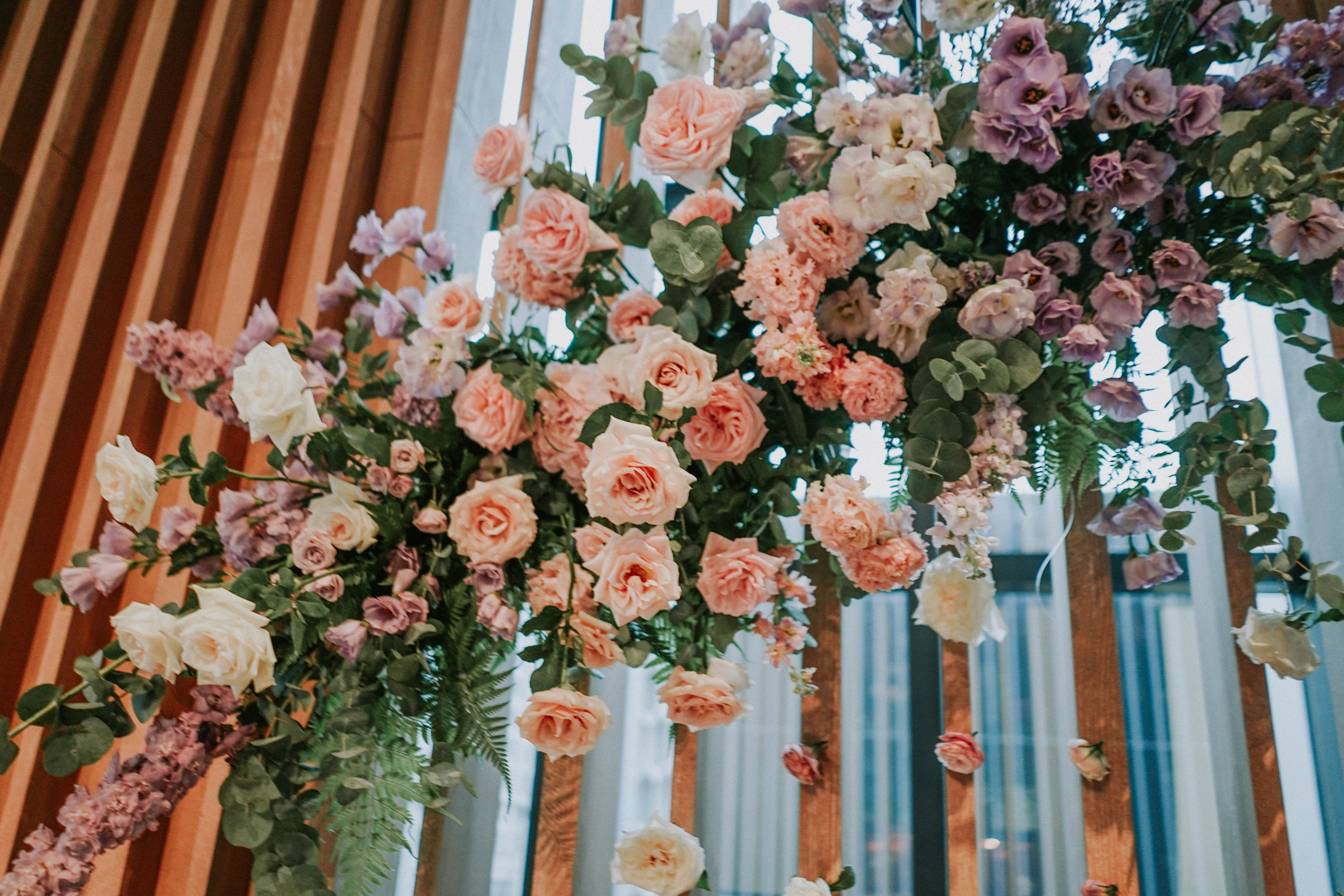 Close up of wedding floral backdrop arrangement with dainty dripping flowers hanging from the trellis at Andaz Hotel main hall