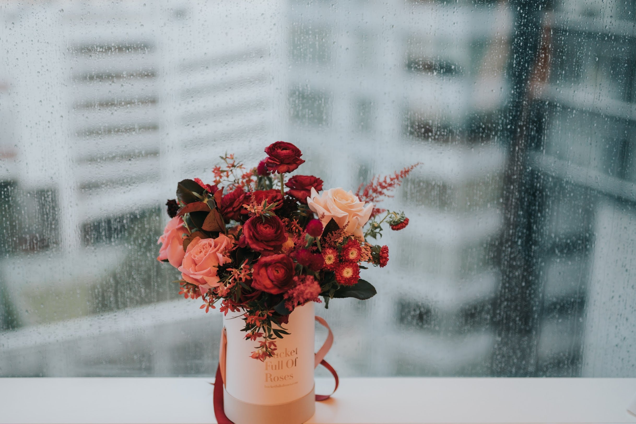 Rainy wedding at St Regis Hotel background with close up shot of bridal bouquet in BFOR packaging to ensure wedding bouquet freshness