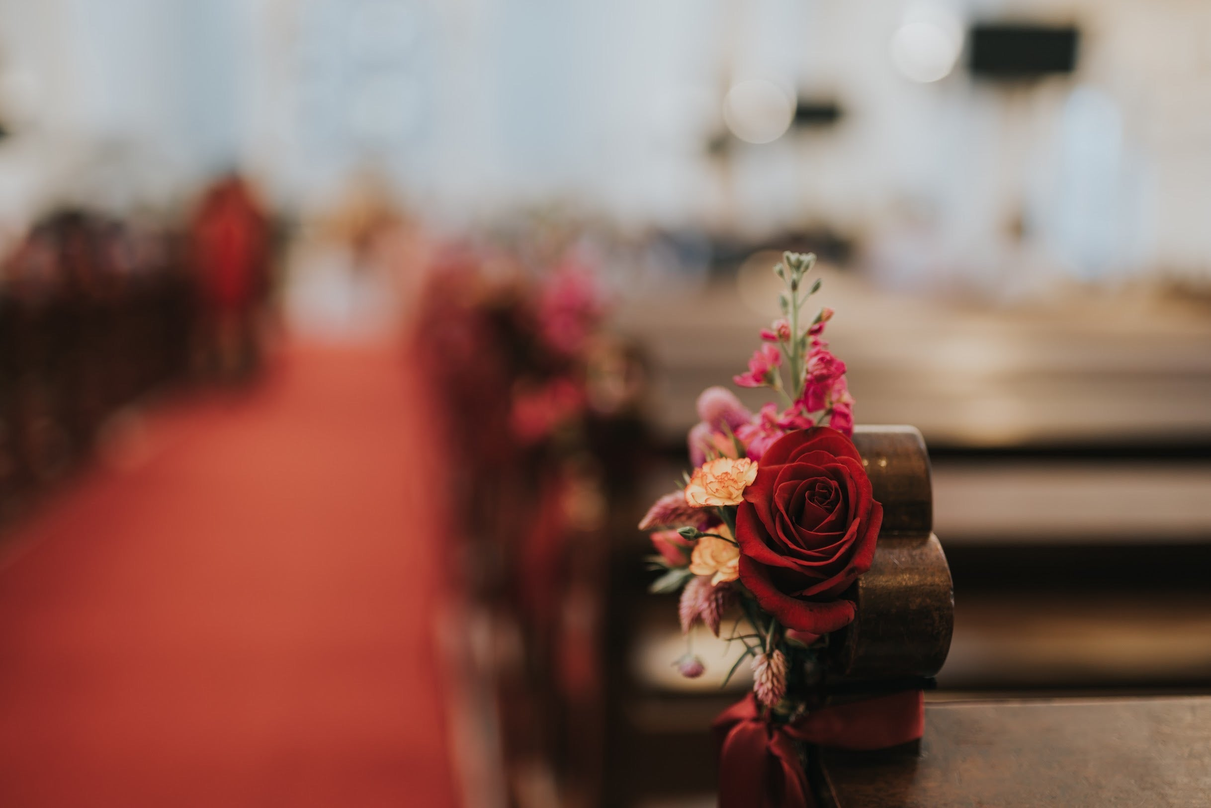 Close up of wedding church pew flower decoration for solemnisation ceremony with eustoma and red roses