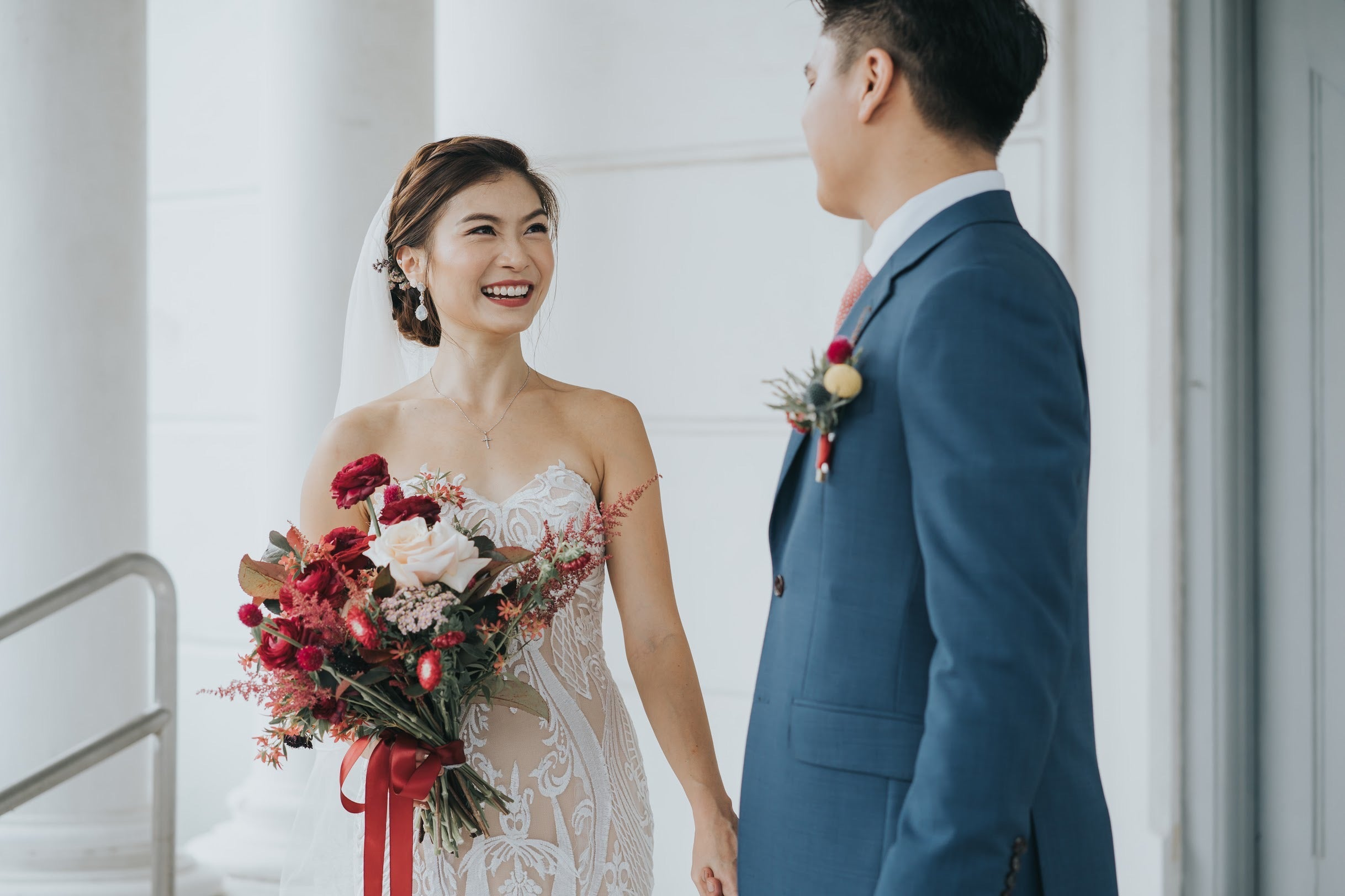 Close up of bridal couple photoshoot with sheer modified A-line wedding dress and coral maroon bridal flower bouquet