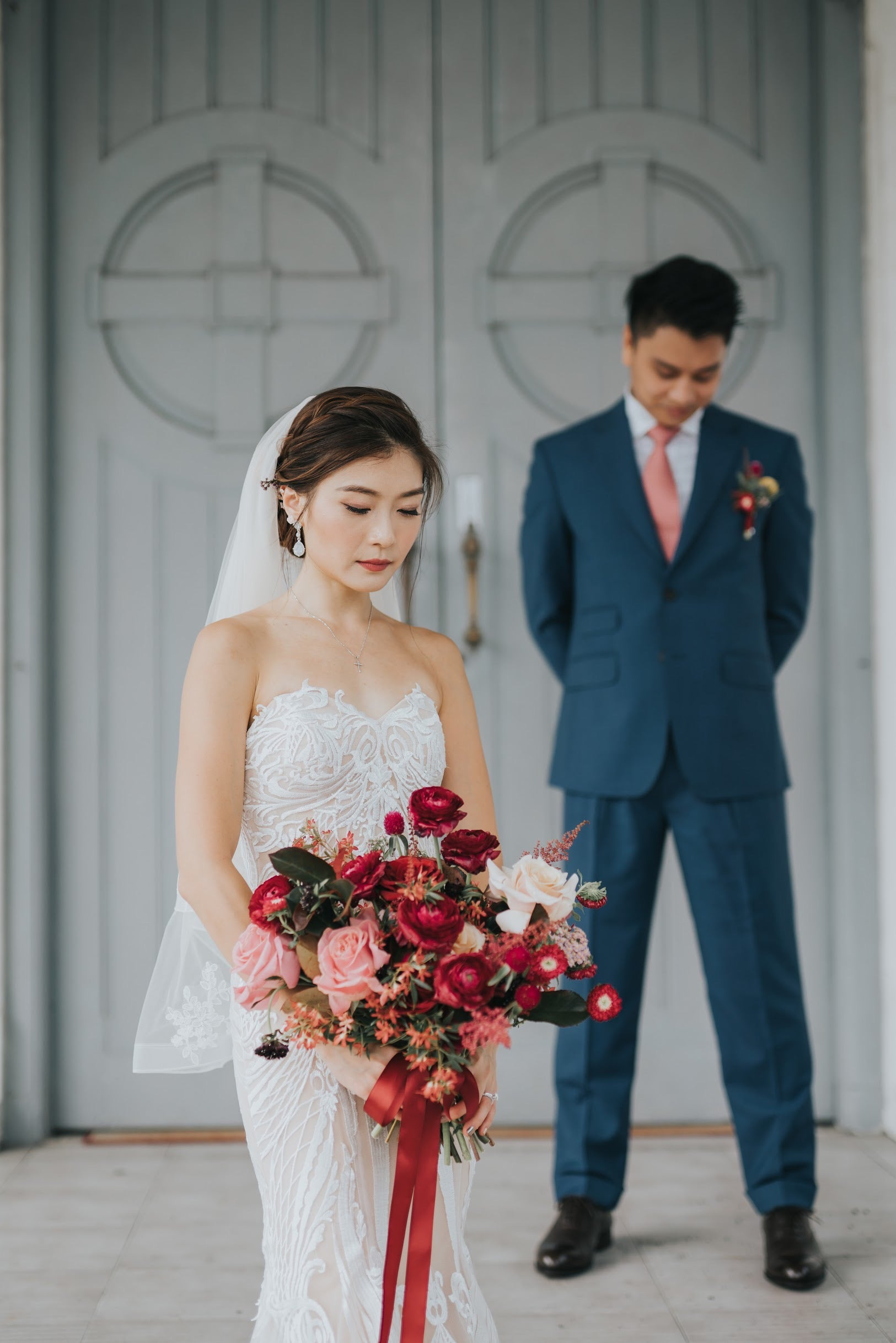 Wedding photoshoot at church venue with bride in foreground wearing a wedding gown with intricate details and holding a rustic red wedding bouquet