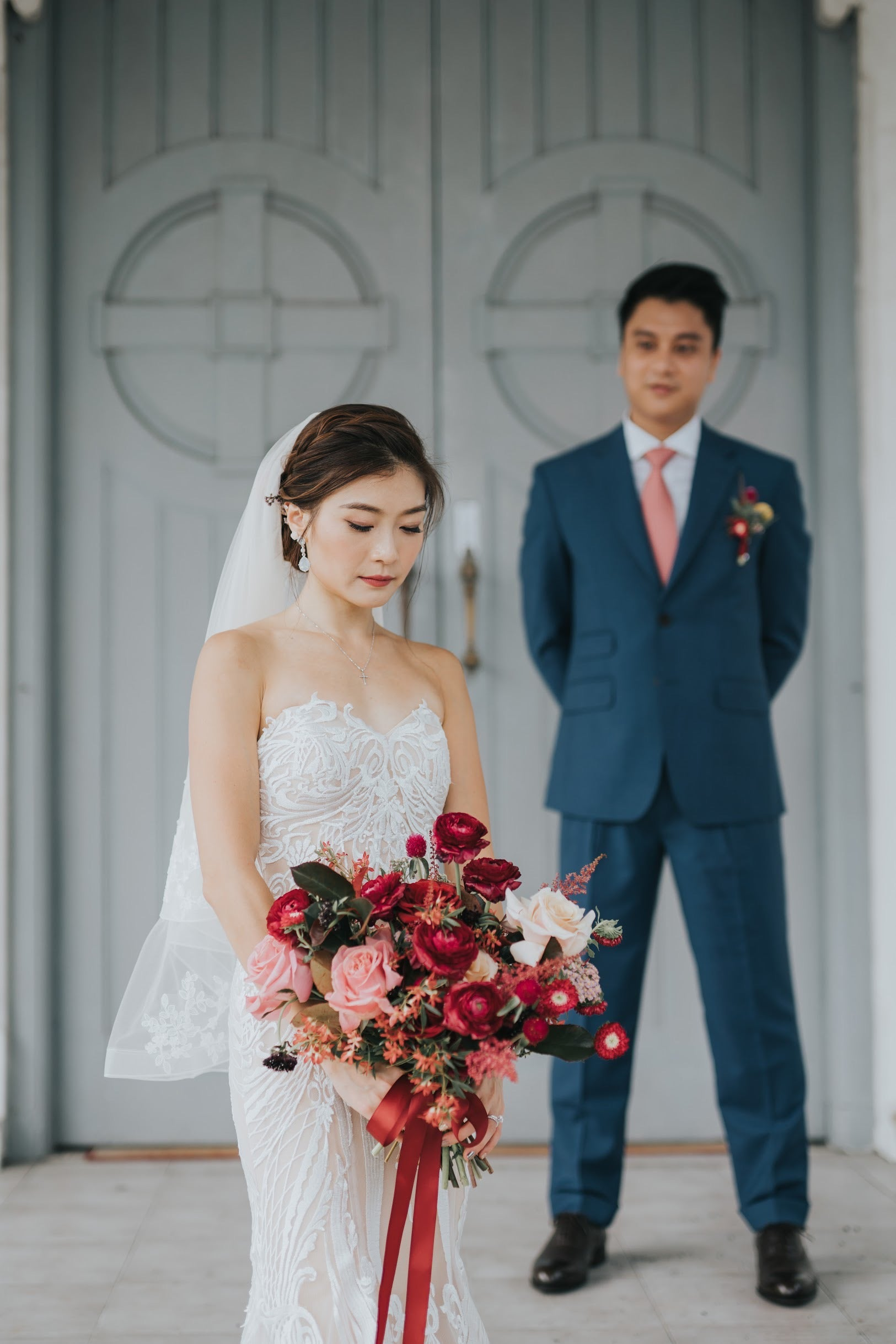 Wedding photoshoot in wedding gown with crimson bridal bouquet and red posy ribbon