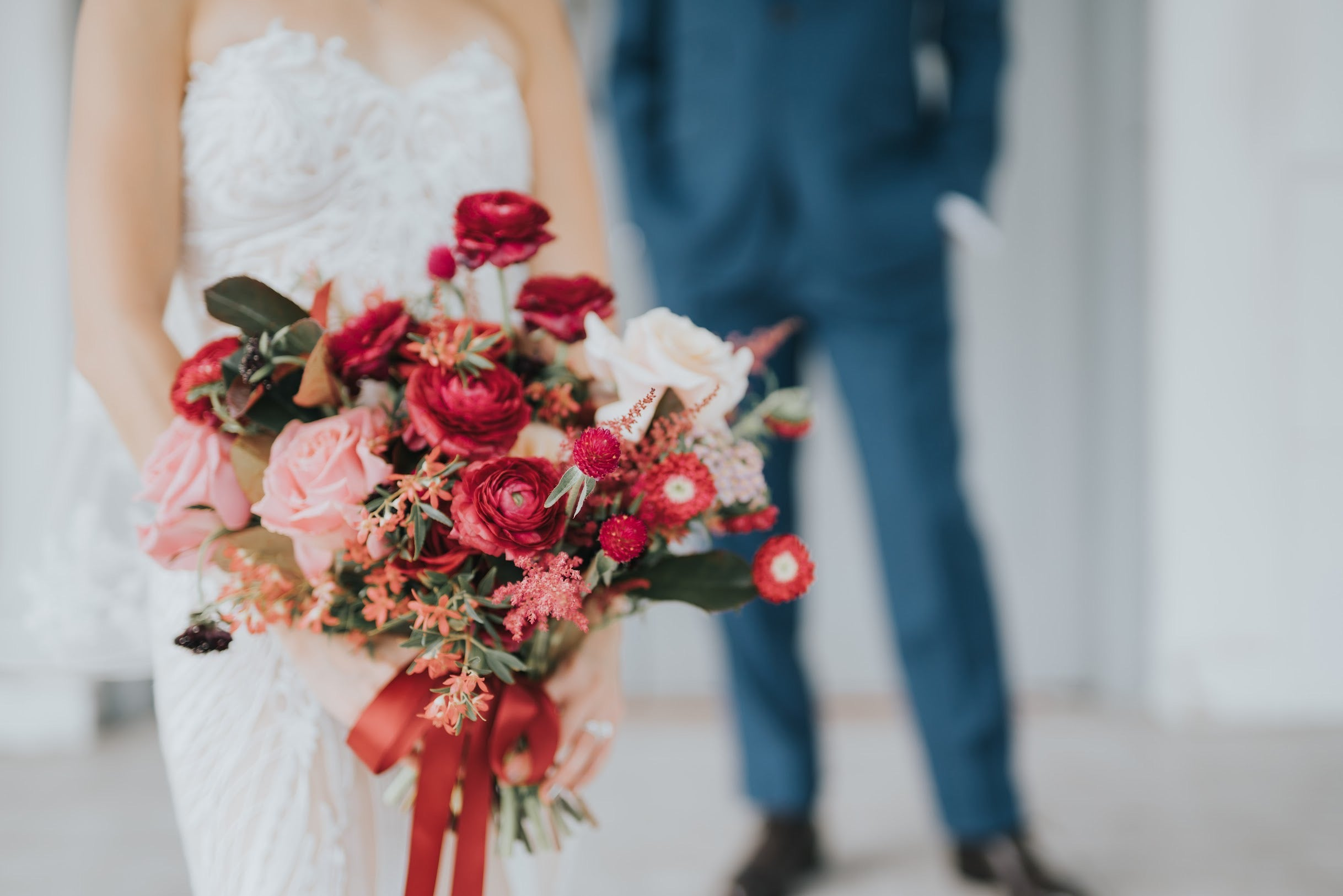Close up of bride bouquet tied with red ribbon with groom in blue suit in background