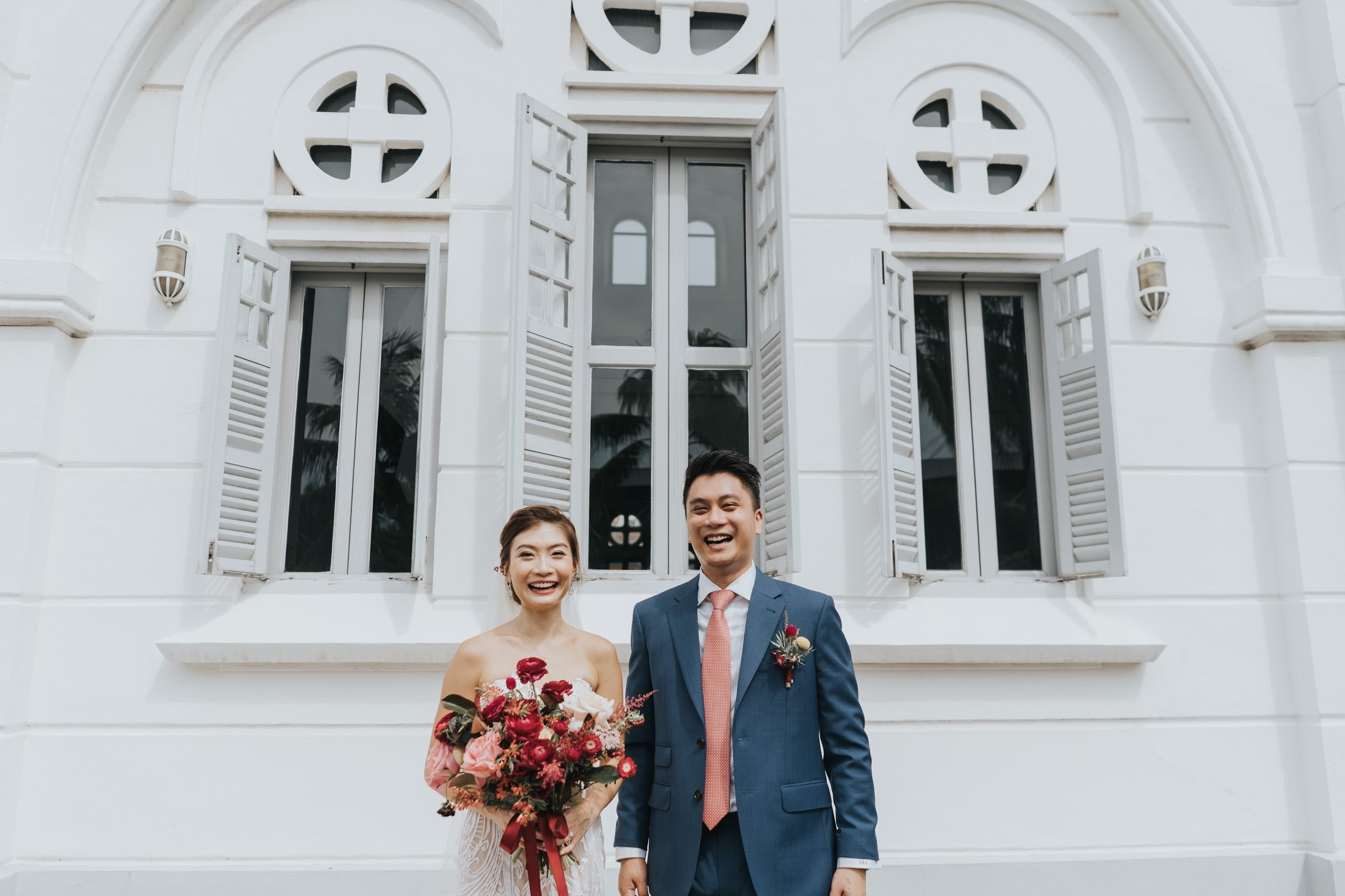 Beaming couple for afternoon wedding shoot outside beautiful louvre windows