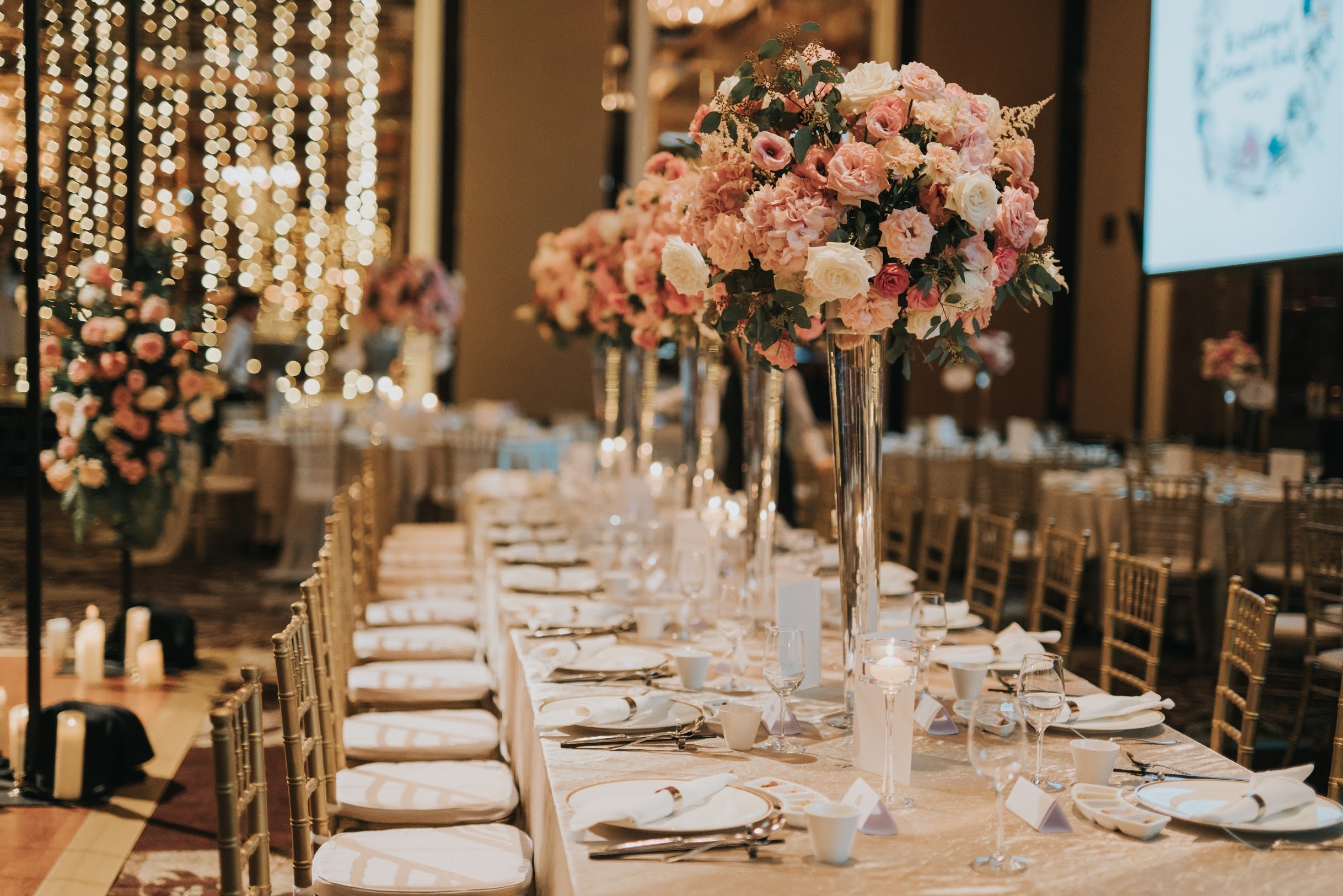 Long dining tables with wedding guests with wedding floral table arrangements in tall crystal vase