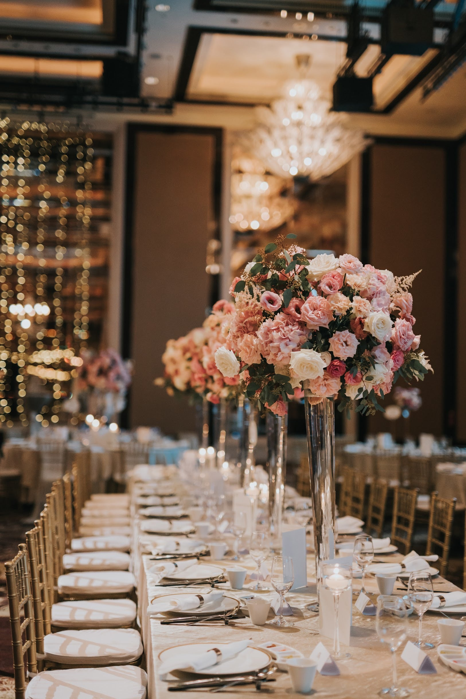Warm real candles next to modern tall crystal vase arrangements for round table flower centerpieces