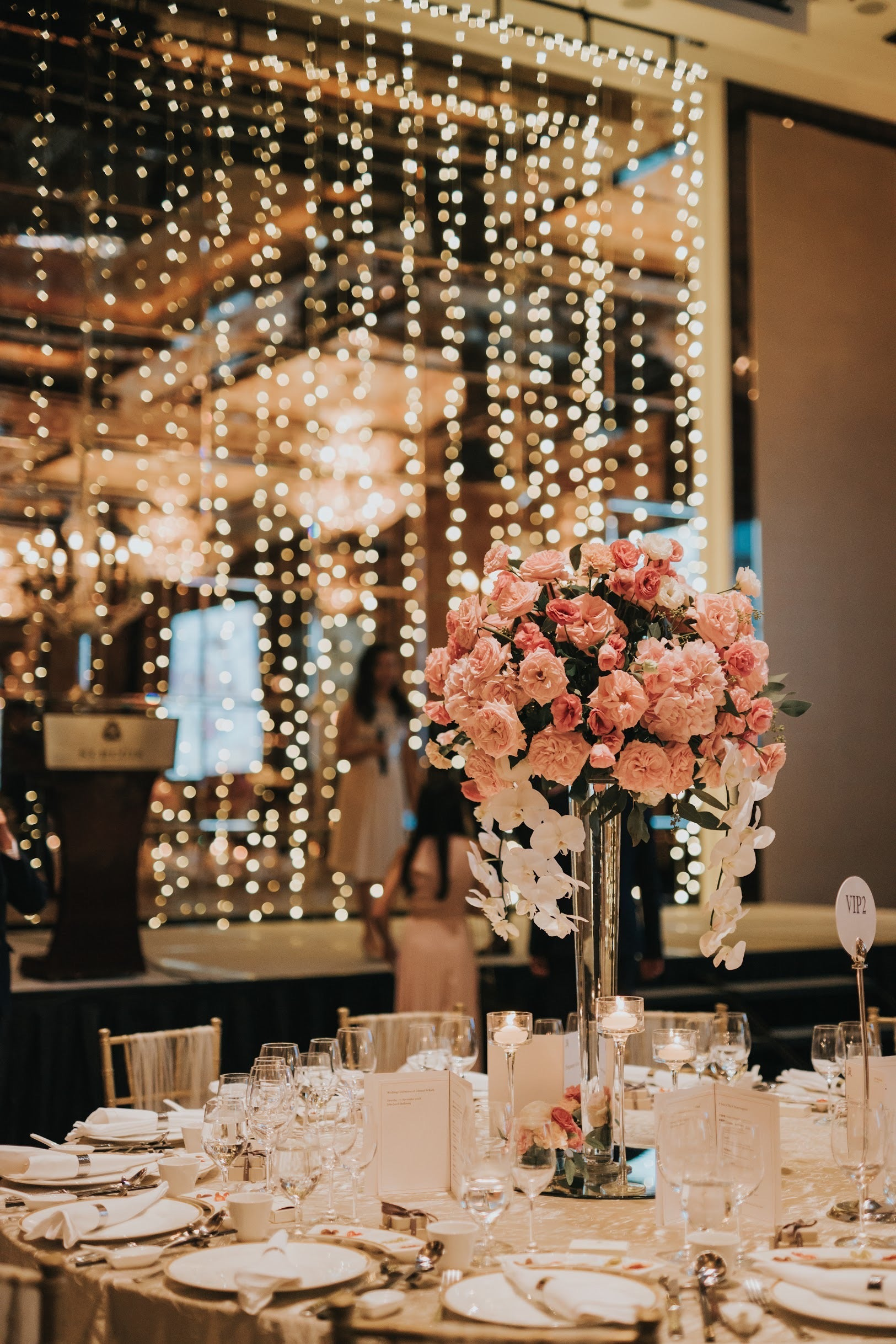 St Regis stage decoration with fairy lights in background with VIP table wedding table roses and orchids