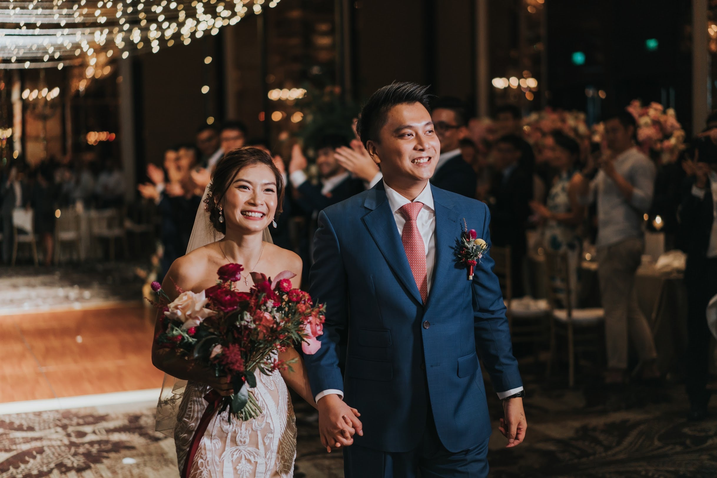 Wedding couple first march in at St Regis aisle of fairy light decor