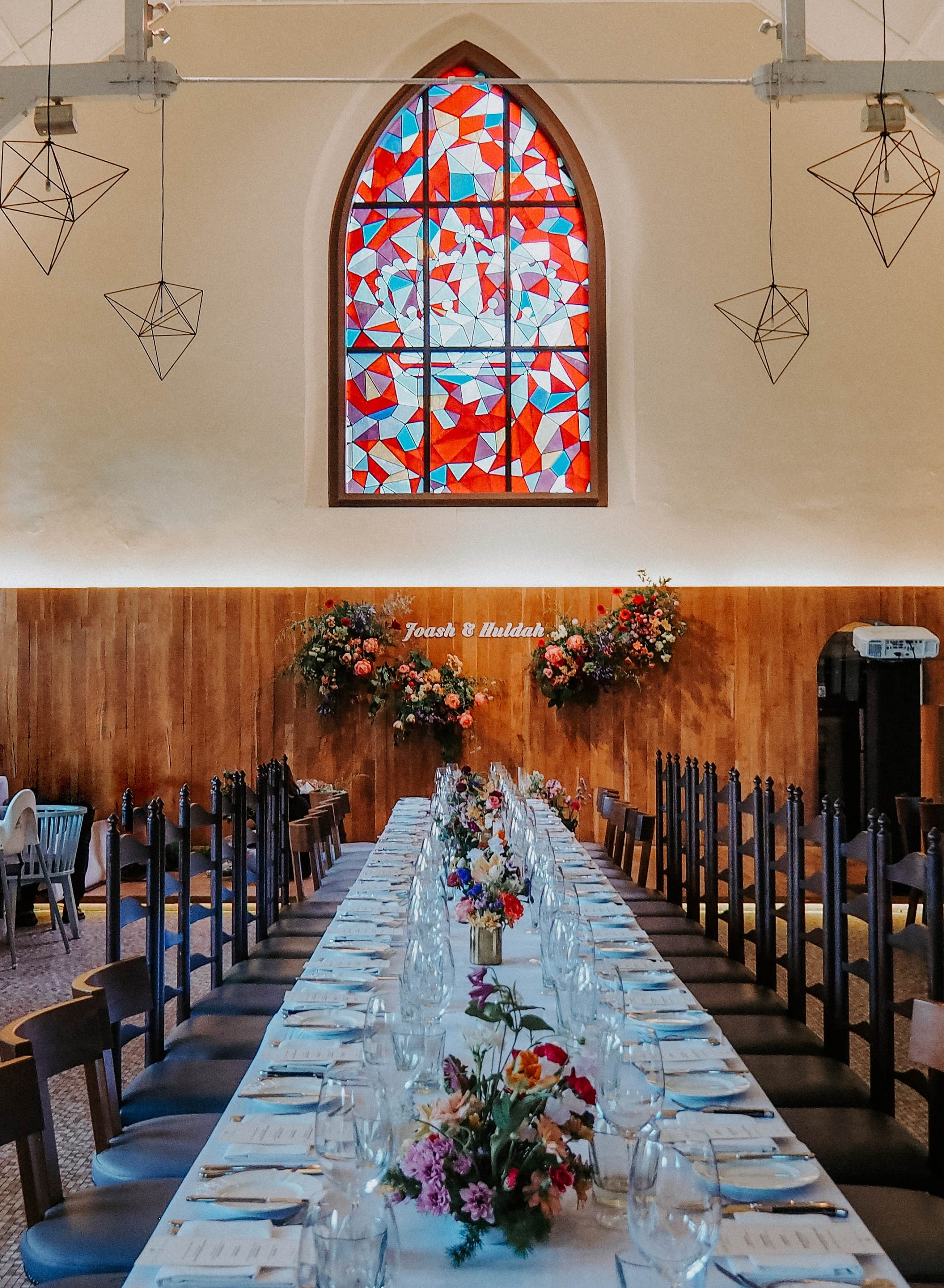 Long wedding table with white linen decorated with themed wedding flowers complementing stained glass windows at Dempsey Hill White Rabbit restaurant Singapore