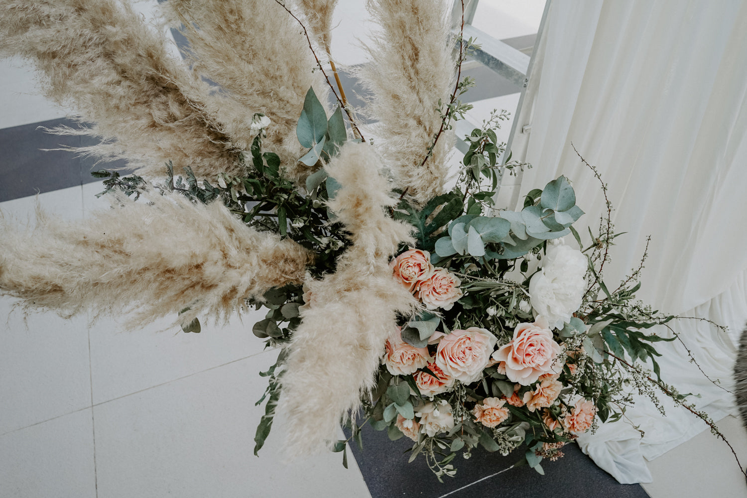 Close up of floral arrangement with eucalyptus, rustic pampas, and salmon coloured wax flowers for intimate wedding at lunch