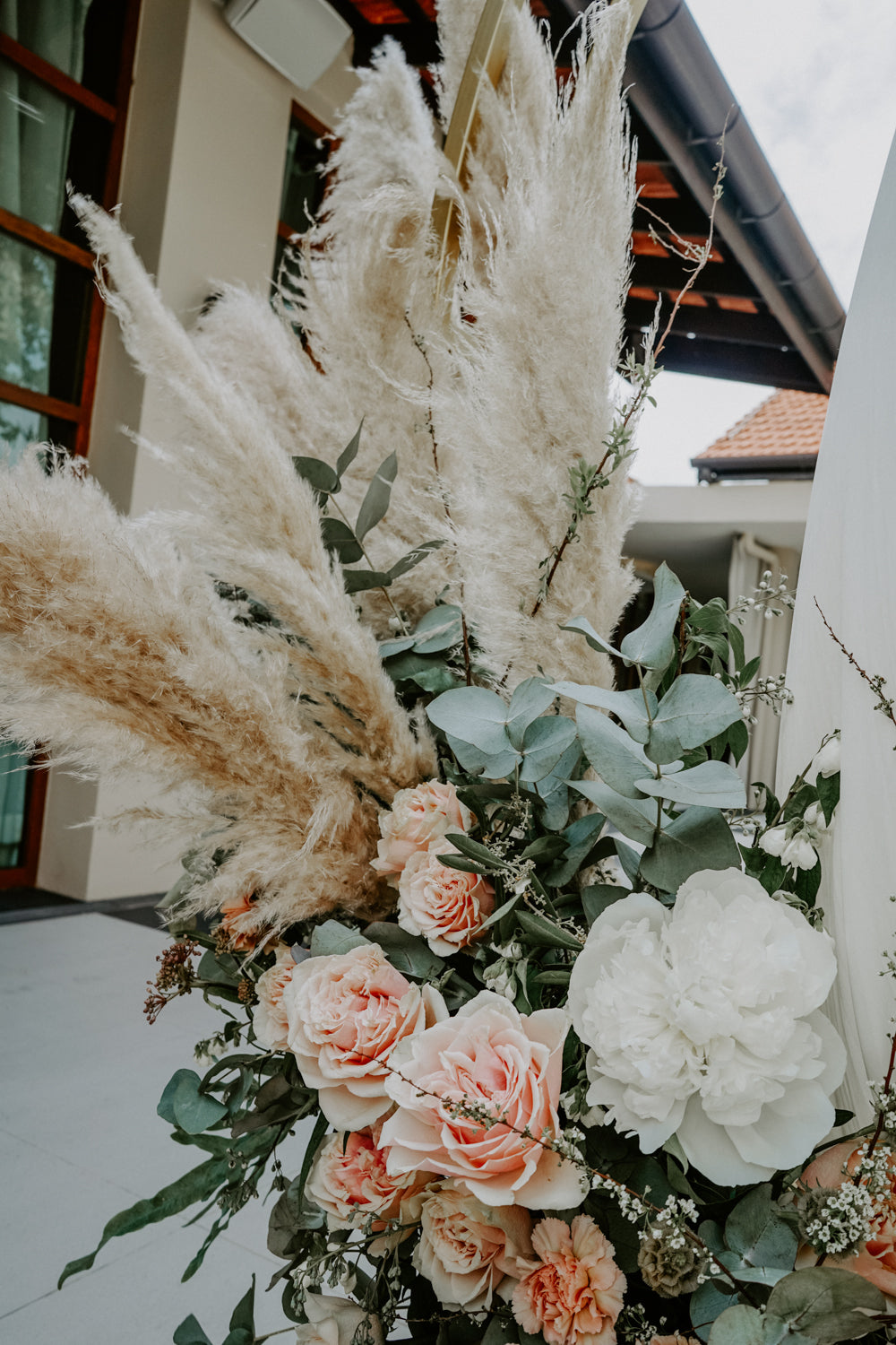 Pampas styled with eucalyptus with pink and white carnations and peonies on a gold floral arch at Sentosa Sofitel hotel Singapore for afternoon solemnisation