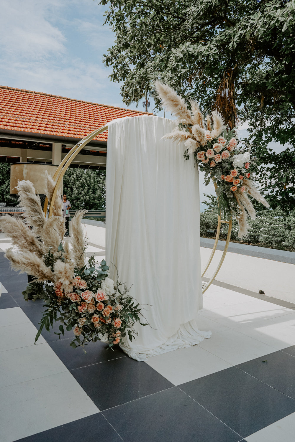 Quaint golden floral arch at Sentosa Sofitel Singapore at lunch solemnization, styled with coral and peachy blooms and dried flowers and elements