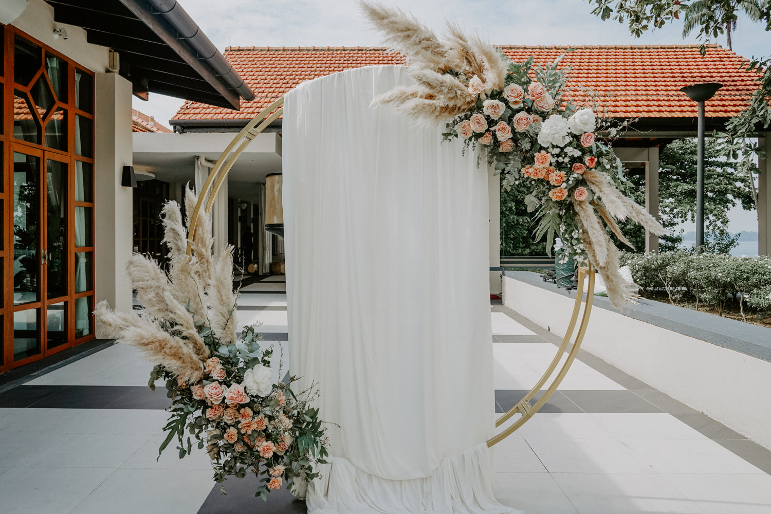 Flower arch, round, golden, set against afternoon sun at Sofitel Hotel Singapore for lunch wedding at Sentosa