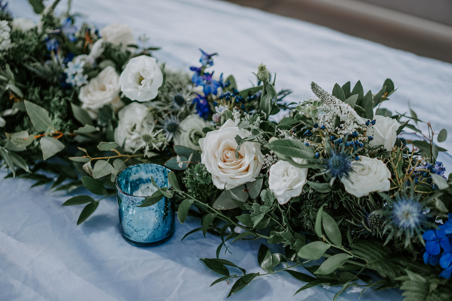 White roses and greenery table arrangement