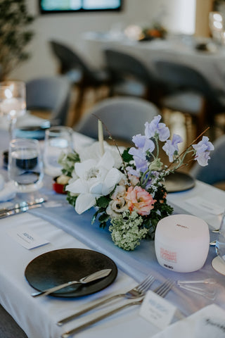 White and purple flower centerpiece on dining table