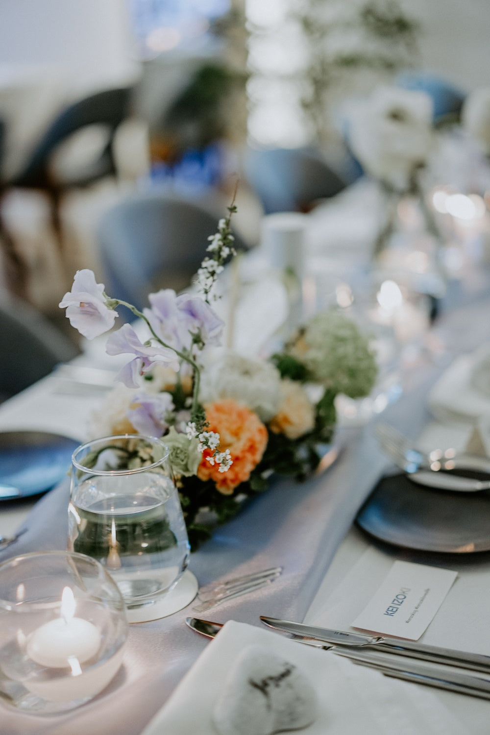 Drinking glass and candles next to purple and orange flower centerpiece