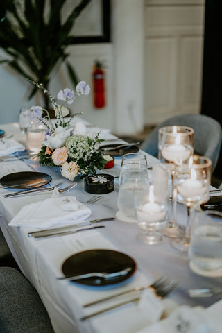 Dinnerware set up on white table and candles