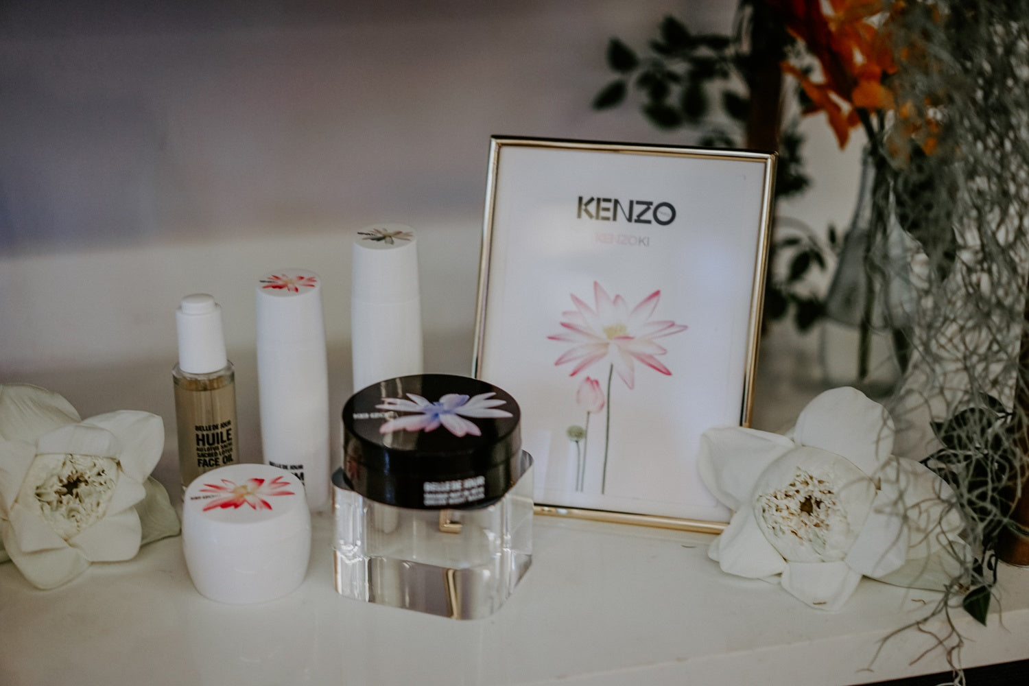 Kenzo picture frame and skincare items with white lotus bud on table